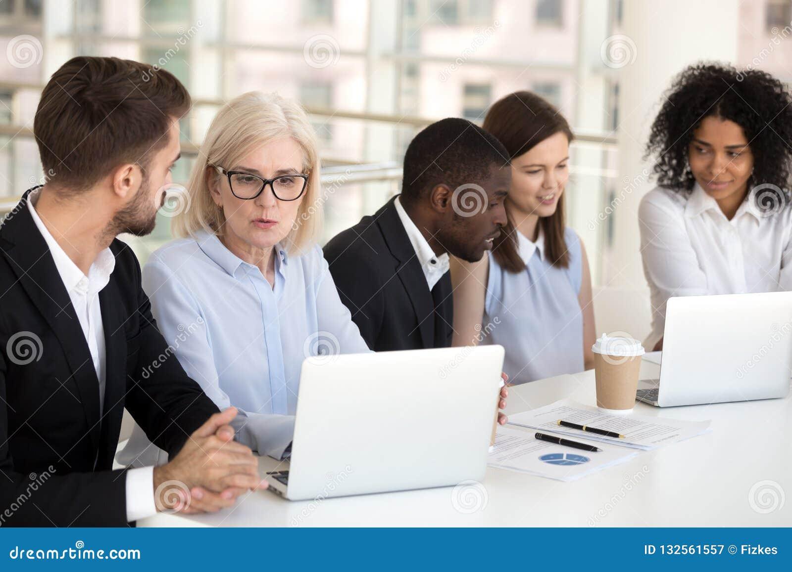 Grupo diverso enfocado serio o de trabajo que habla de los empleados de oficina