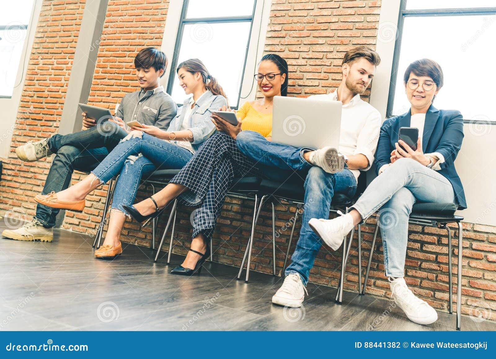 Grupo diverso multiétnico de gente joven y adulta que usa el smartphone, ordenador portátil, tableta digital junto