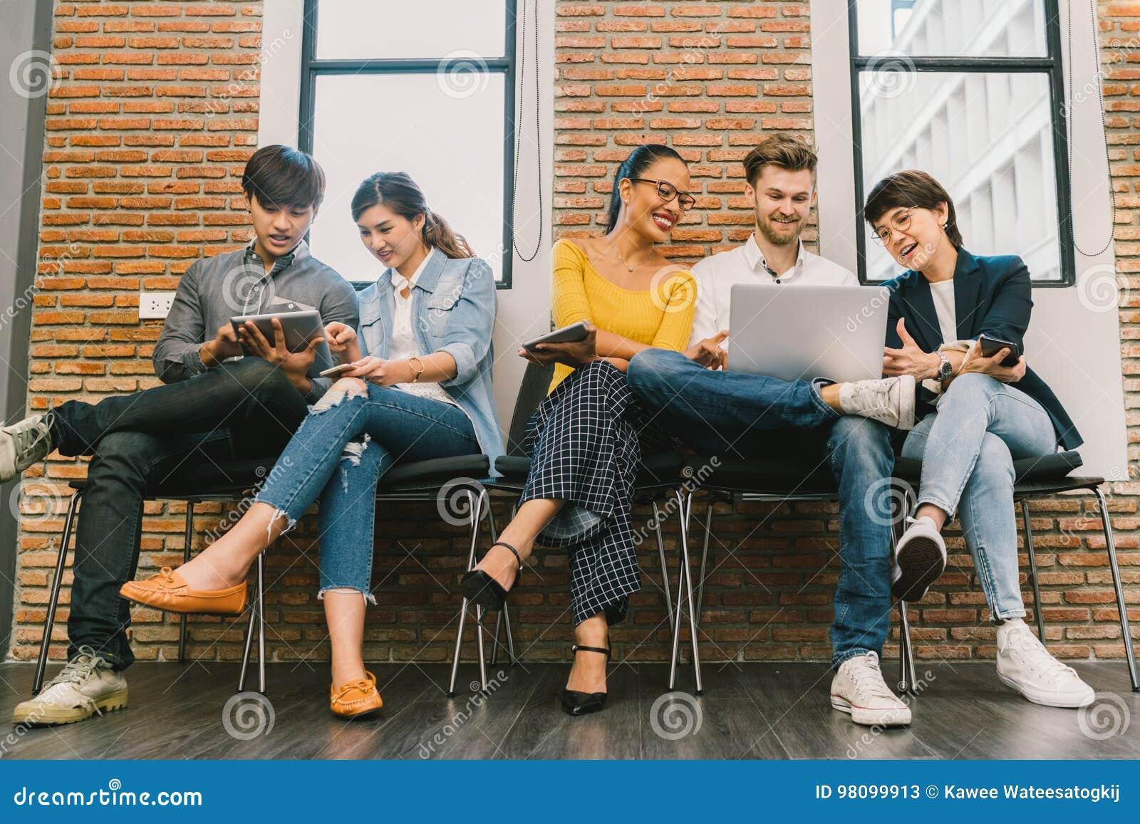 Grupo diverso multi-étnico de povos novos e adultos que usam o smartphone, laptop, tabuleta digital junto