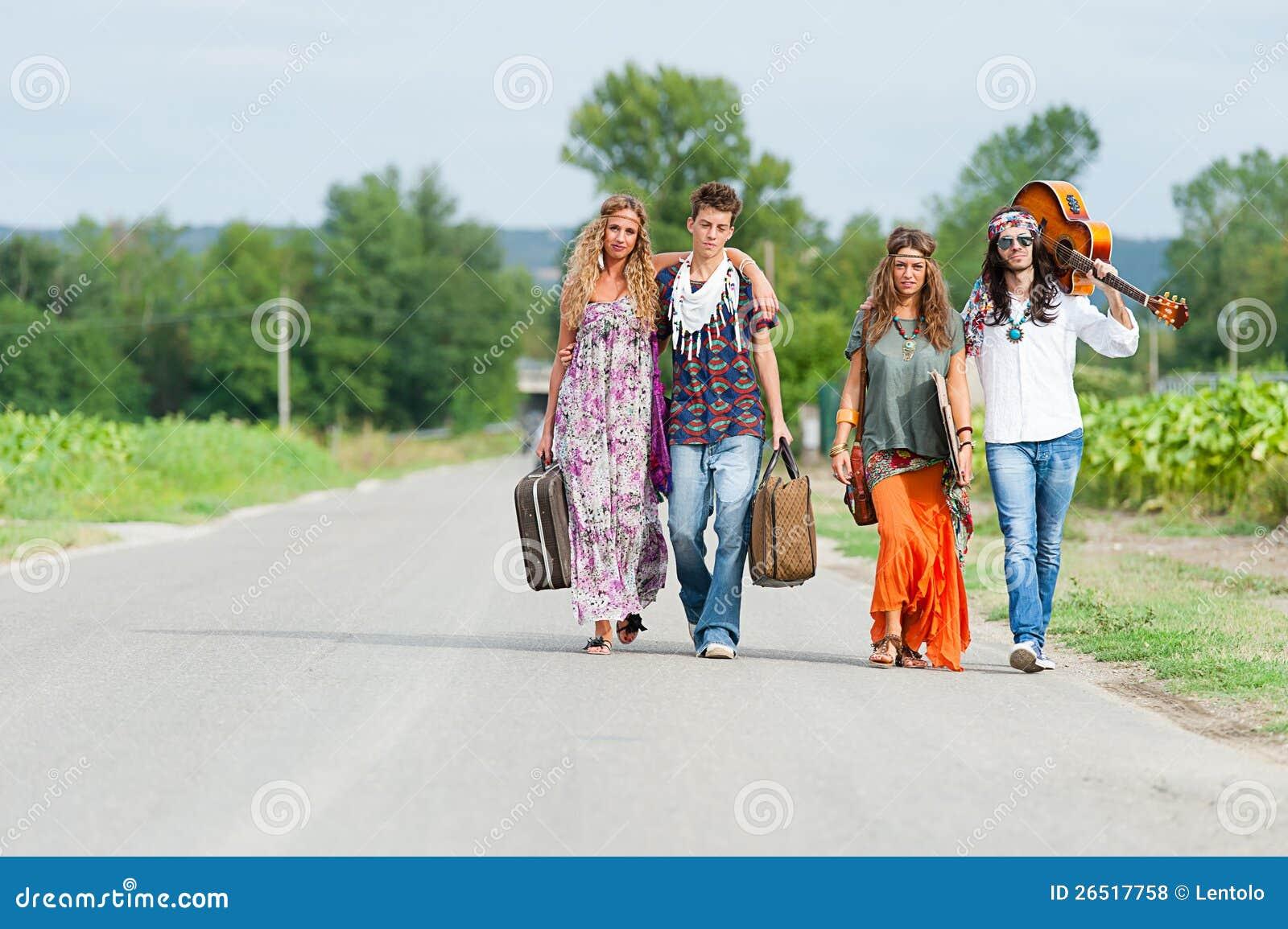 Grupo do Hippie que viaja em uma estrada do campo