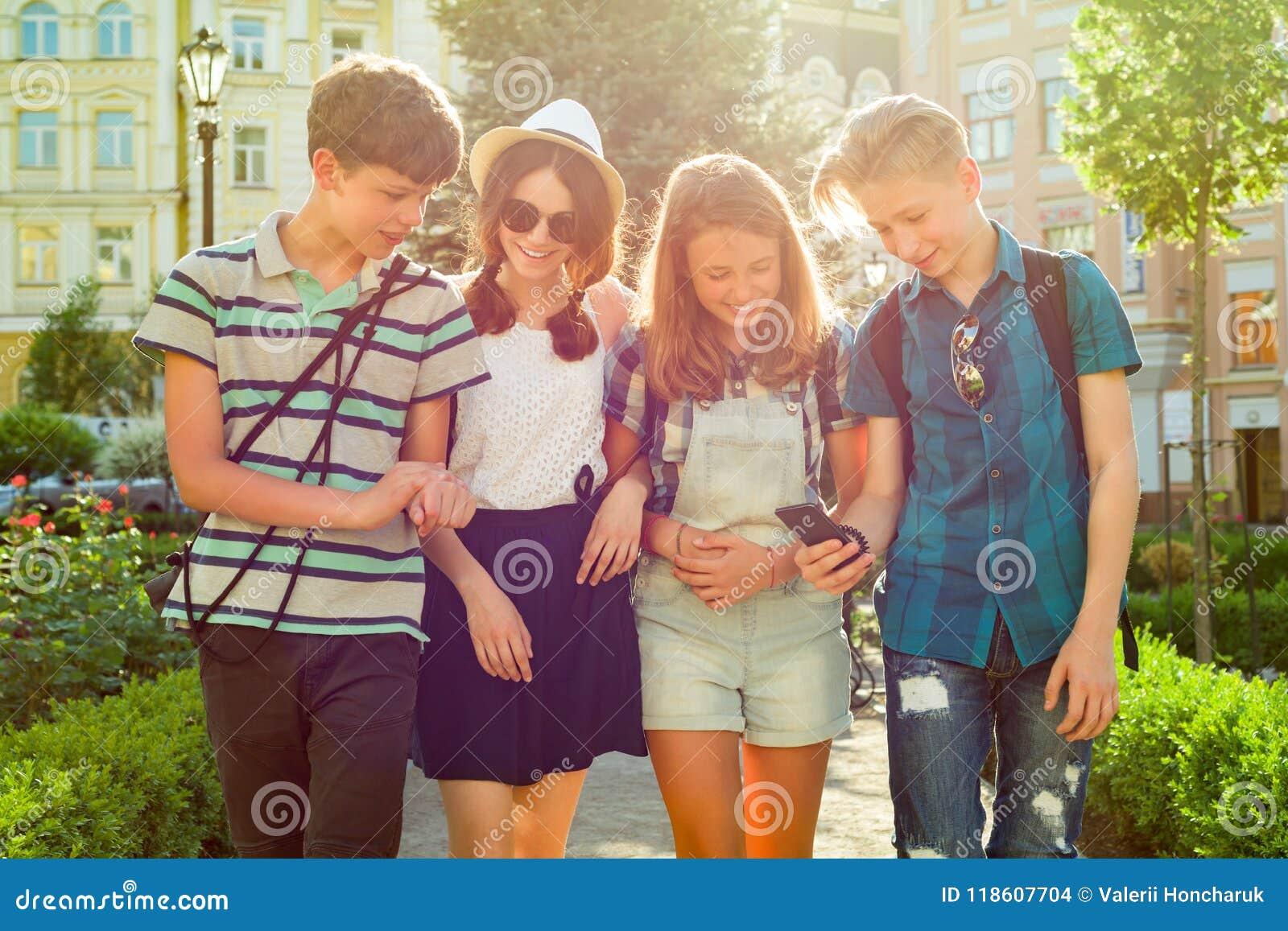 Grupo dos amigos felizes 13 dos adolescentes, 14 anos andando ao longo da rua da cidade