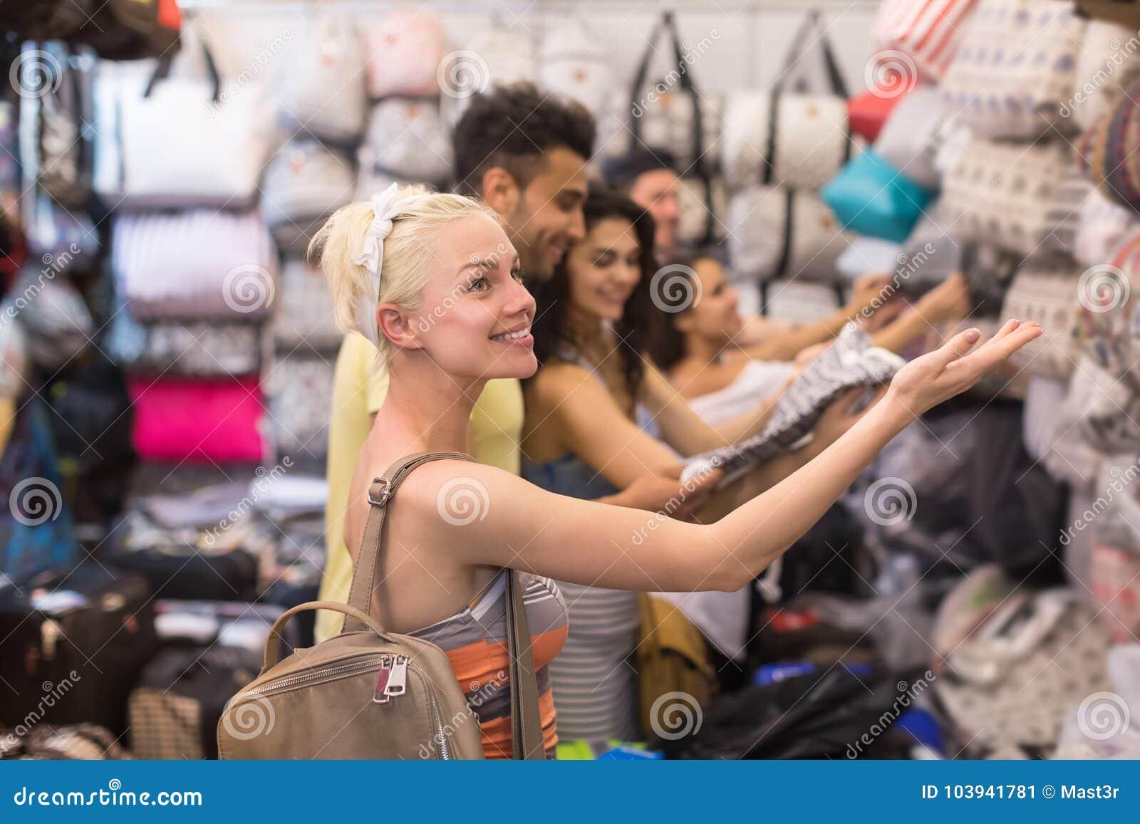 Grupo dos jovens na compra que escolhe compradores de sorriso felizes do saco, do homem e da mulher na loja