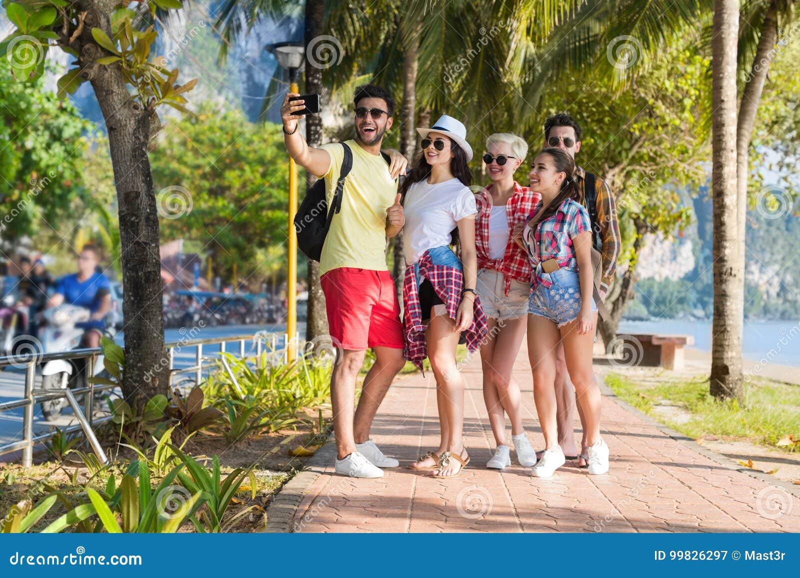 Grupo dos jovens na praia que toma a foto de Selfie em férias de verão espertas do telefone da pilha, feriado de sorriso feliz do