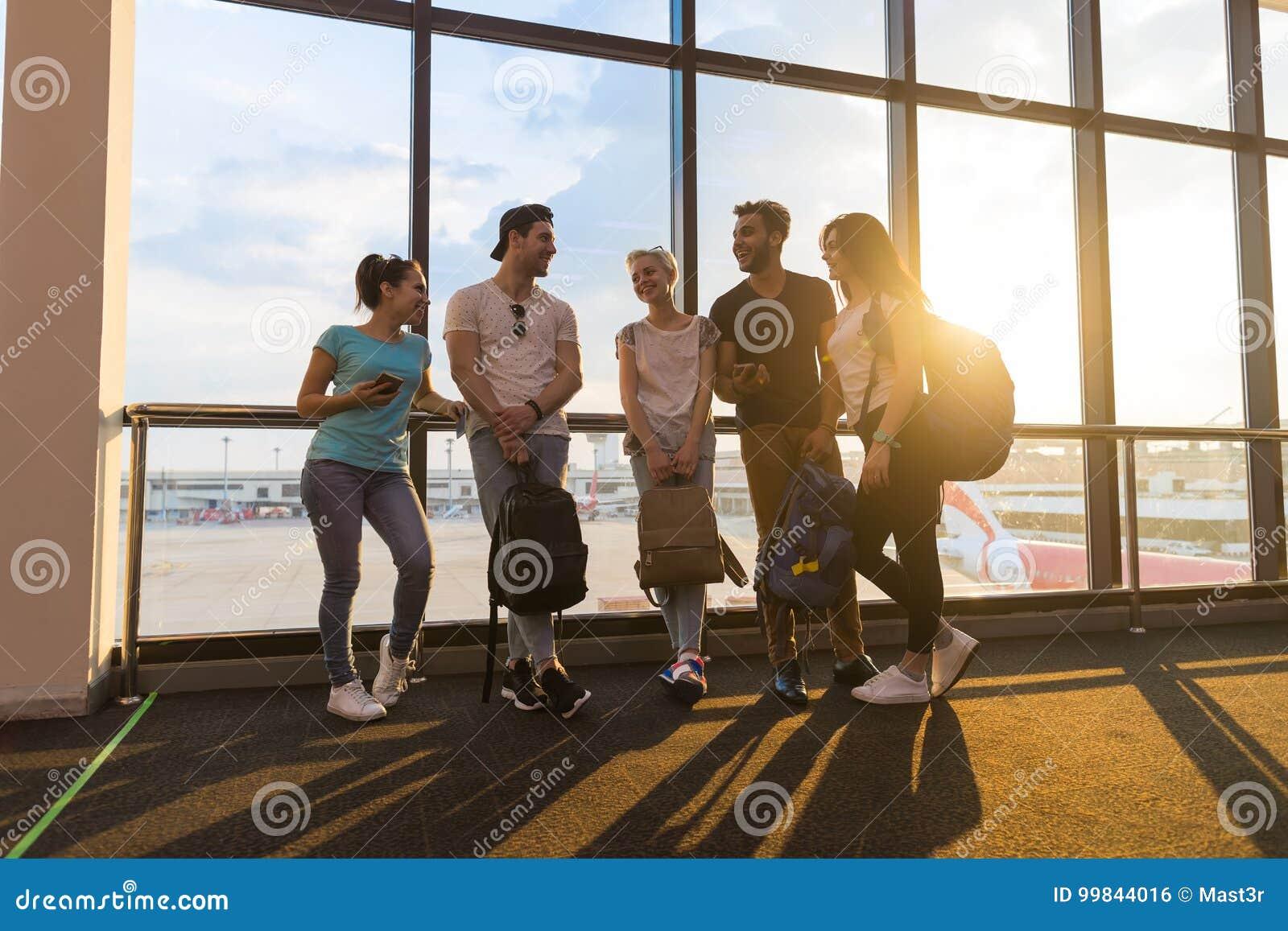 Grupo dos jovens na sala de estar do aeroporto perto da partida de espera de Windows que fala amigos felizes da raça da mistura d
