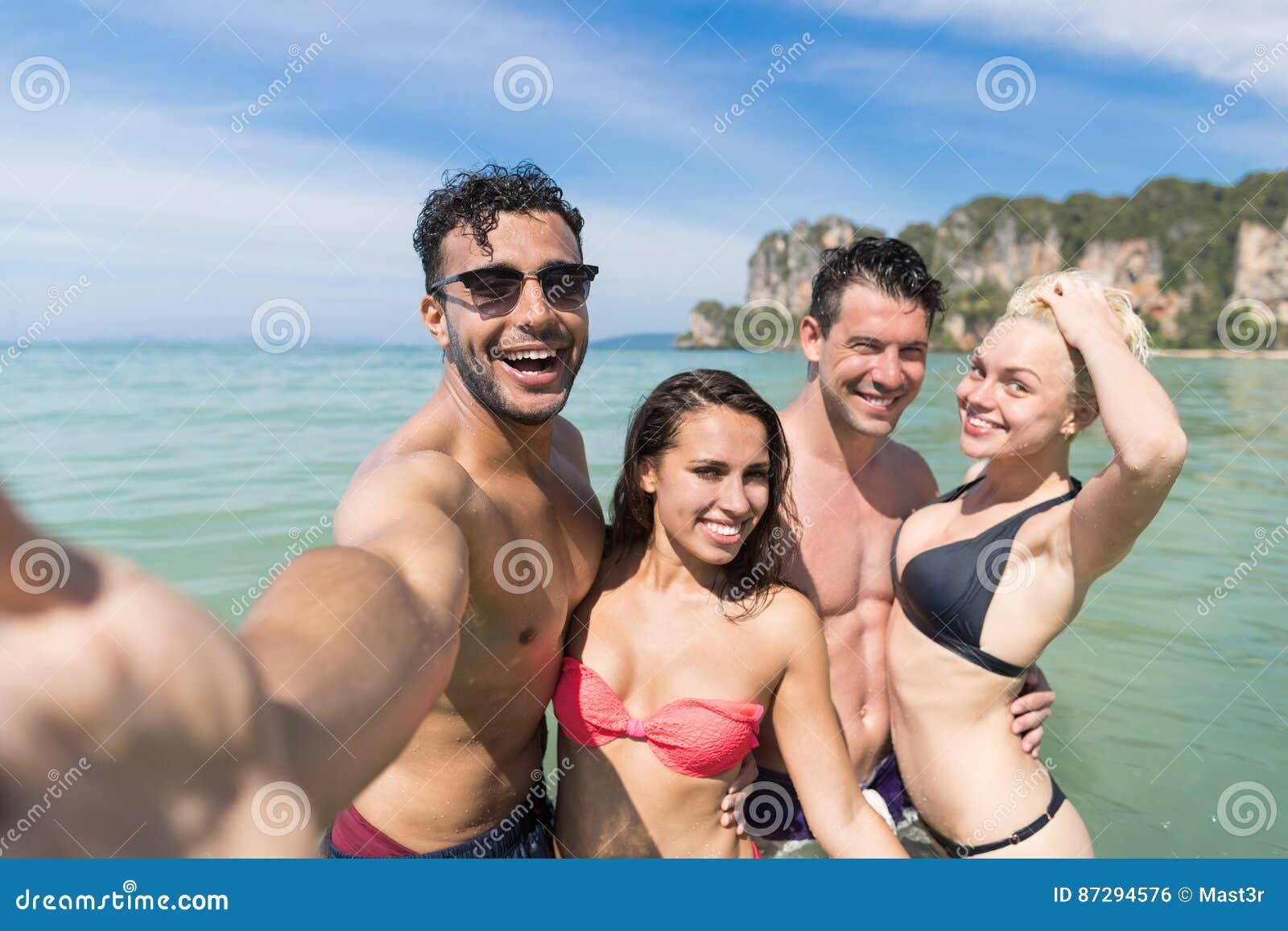Grupo em férias de verão da praia, amigos de sorriso felizes dos jovens que tomam a foto de Selfie no oceano do mar da água