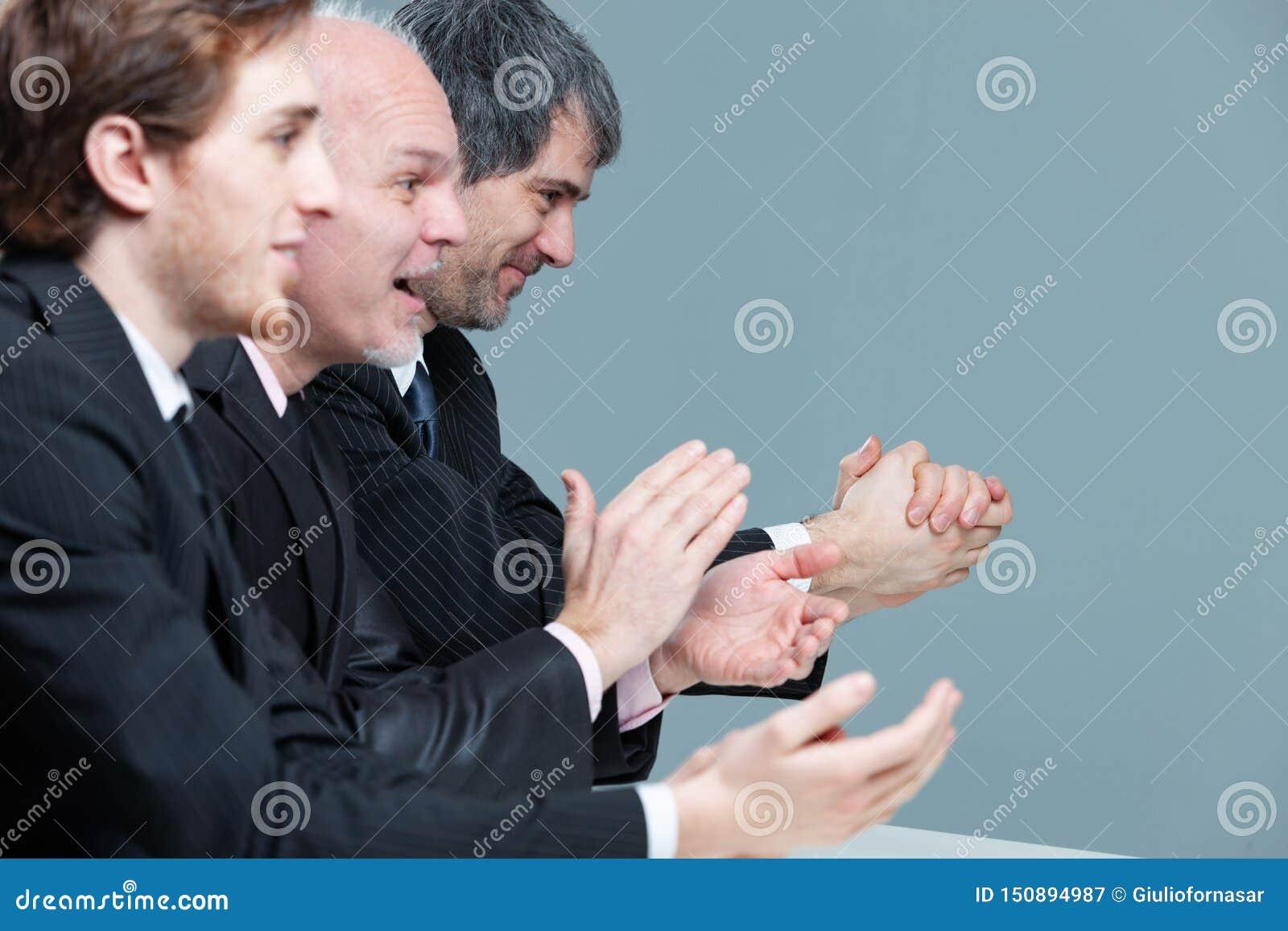 Grupo entusiástico de aplauso do homem de negócios