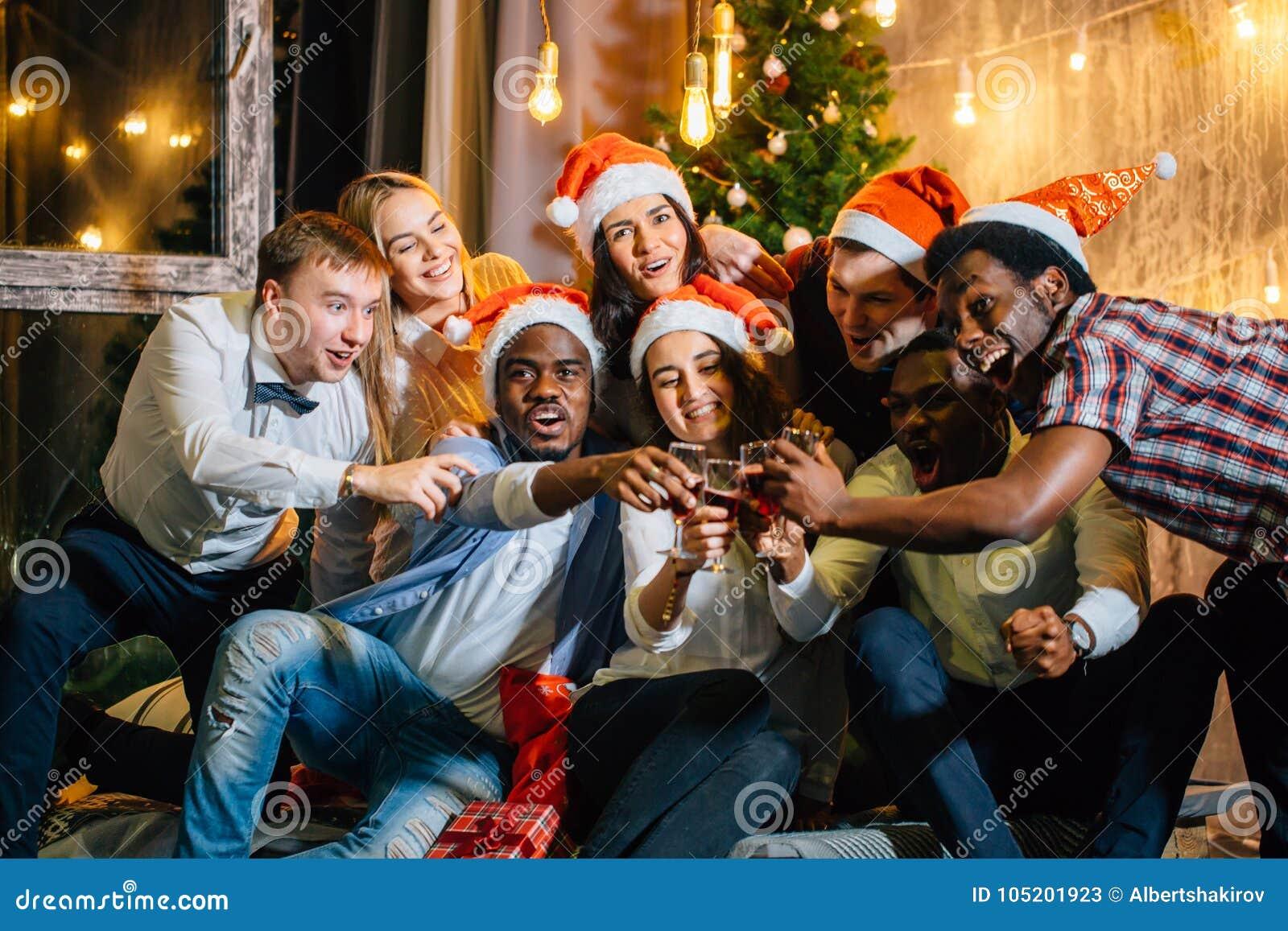 Grupo feliz de amigos que tocam nos glases um com o otro