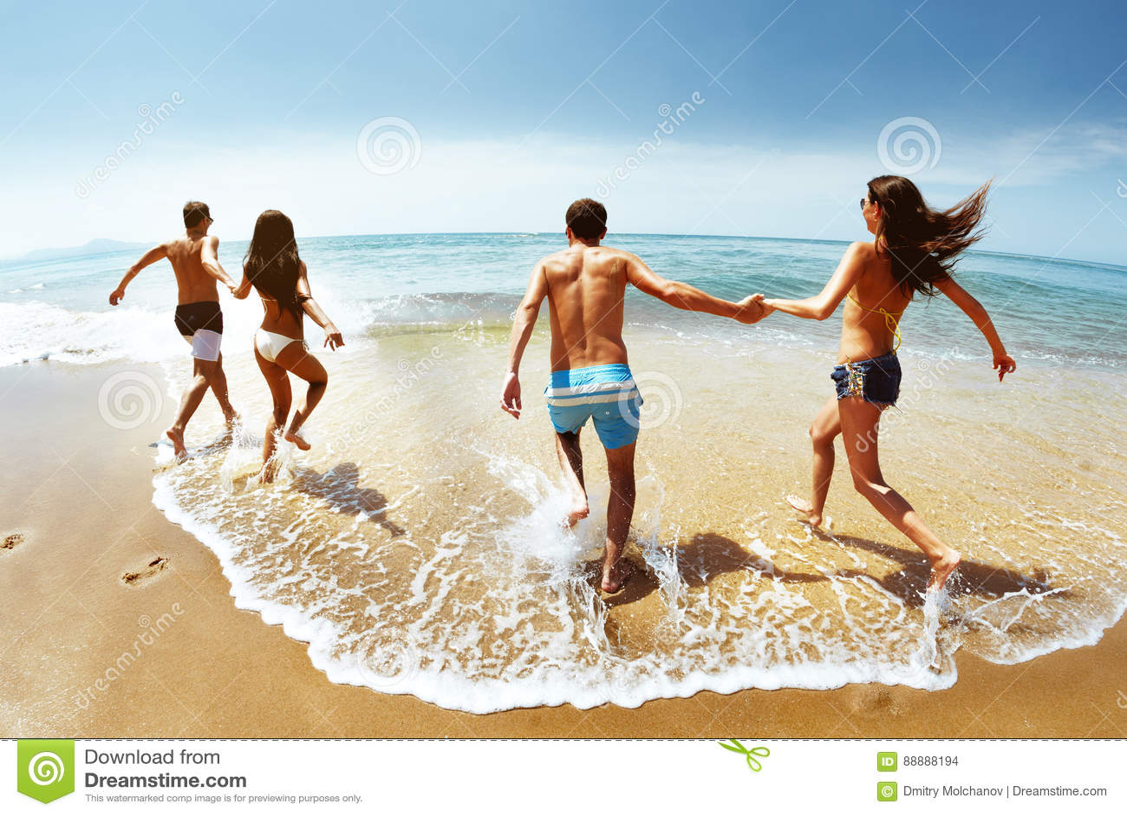 Grupo feliz de funcionamientos de los amigos al mar