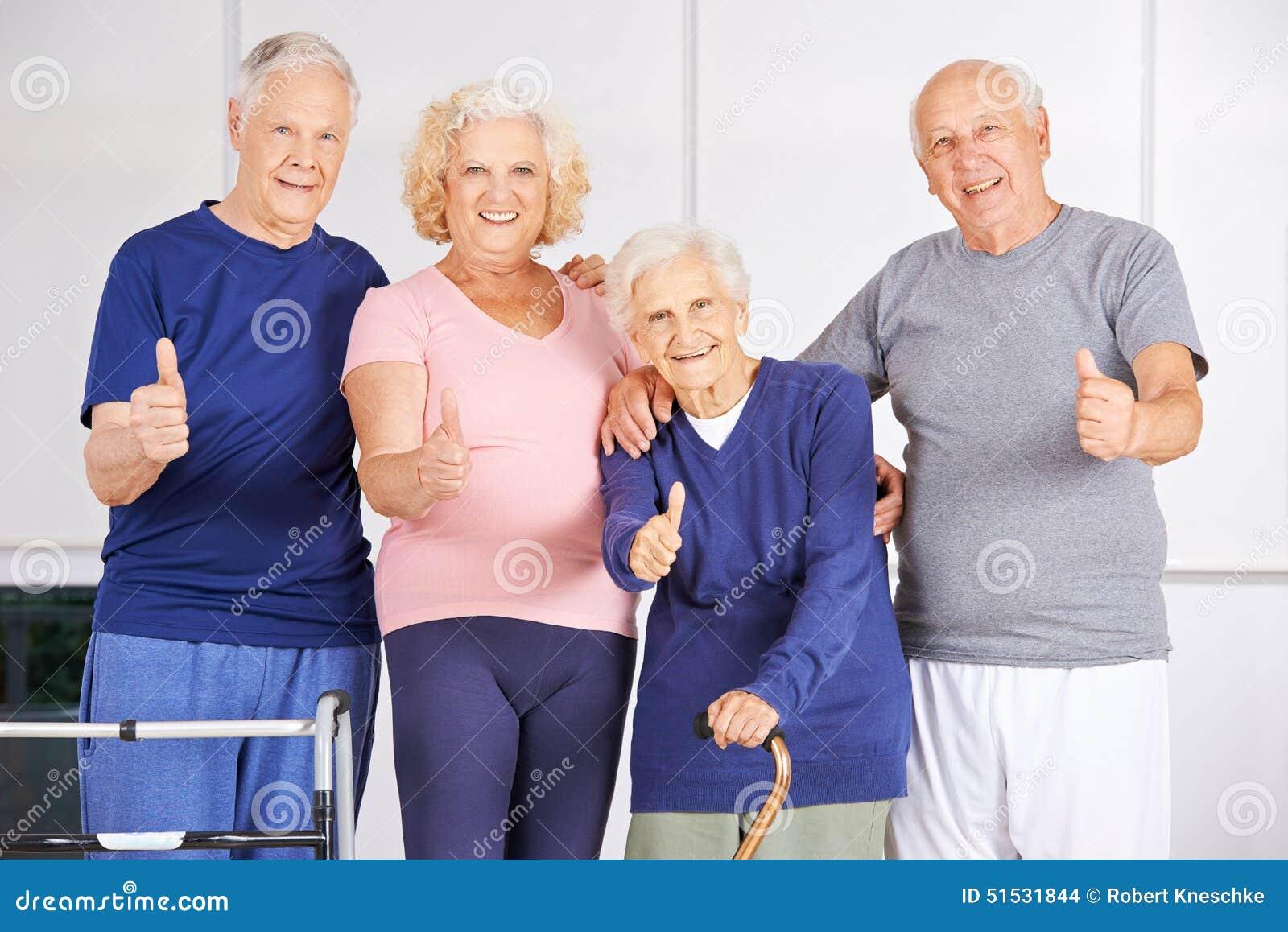 Grupo feliz de sêniores que mantêm os polegares