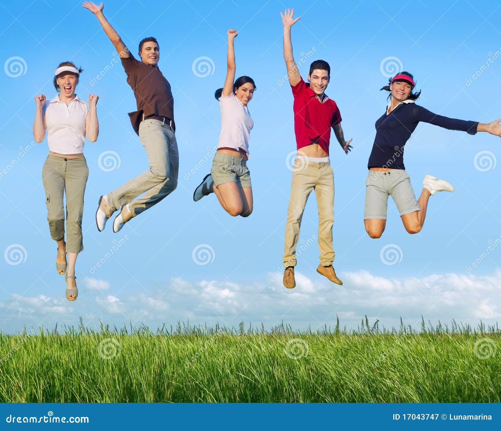 Grupo feliz de salto dos jovens no prado