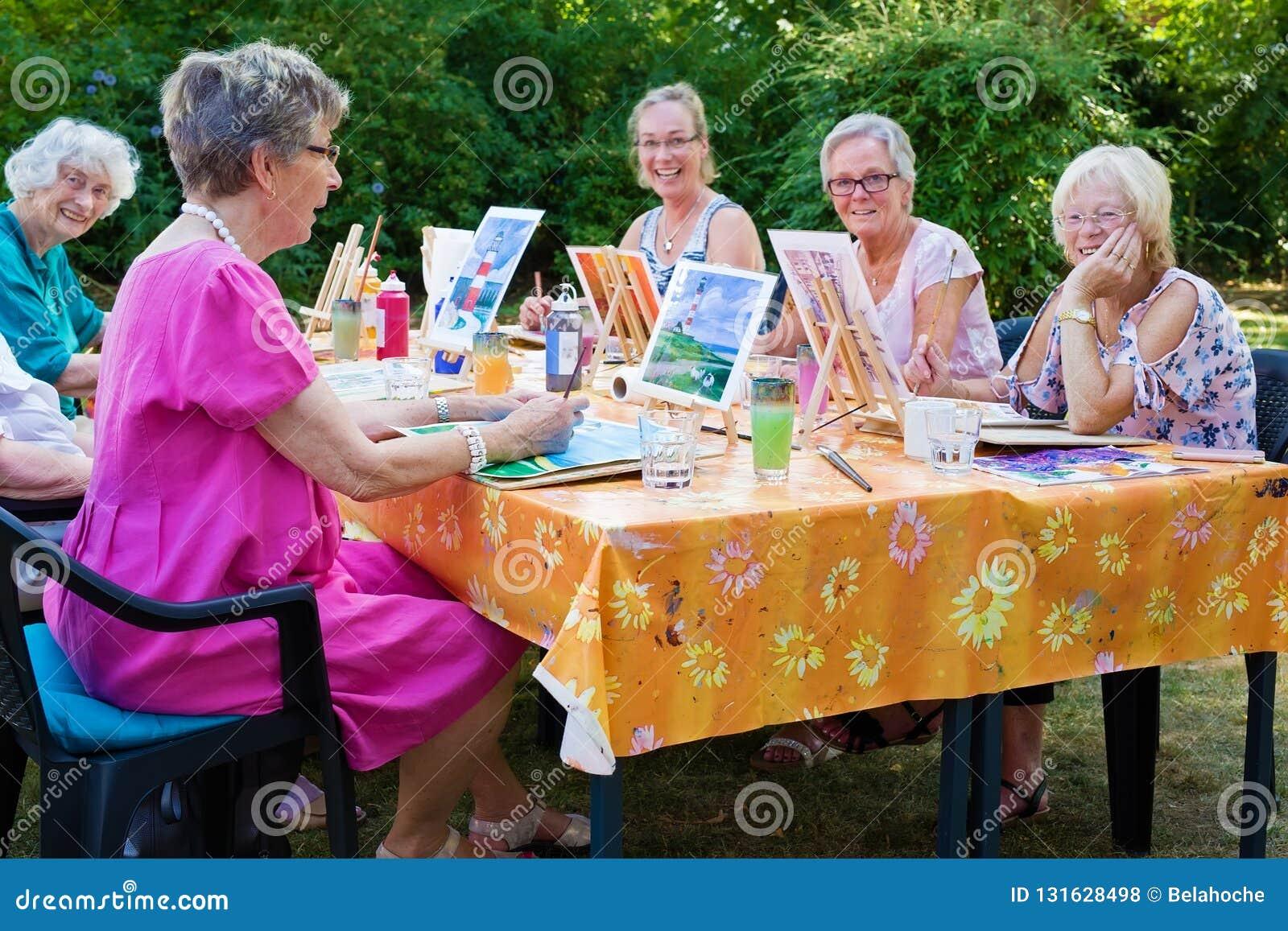 Grupo feliz de senhoras superiores que apreciam a classe de arte assentada em torno de um ar livre da tabela na pintura do jardim
