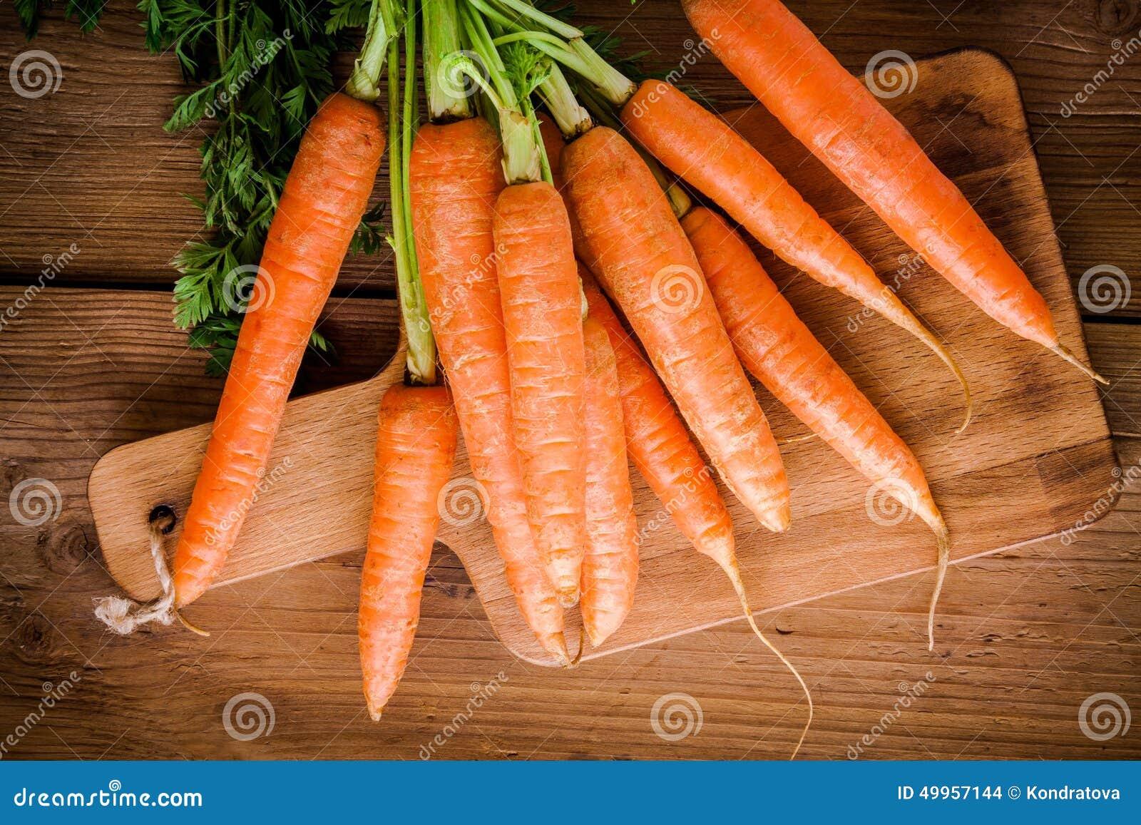 Grupo fresco das cenouras na placa de corte