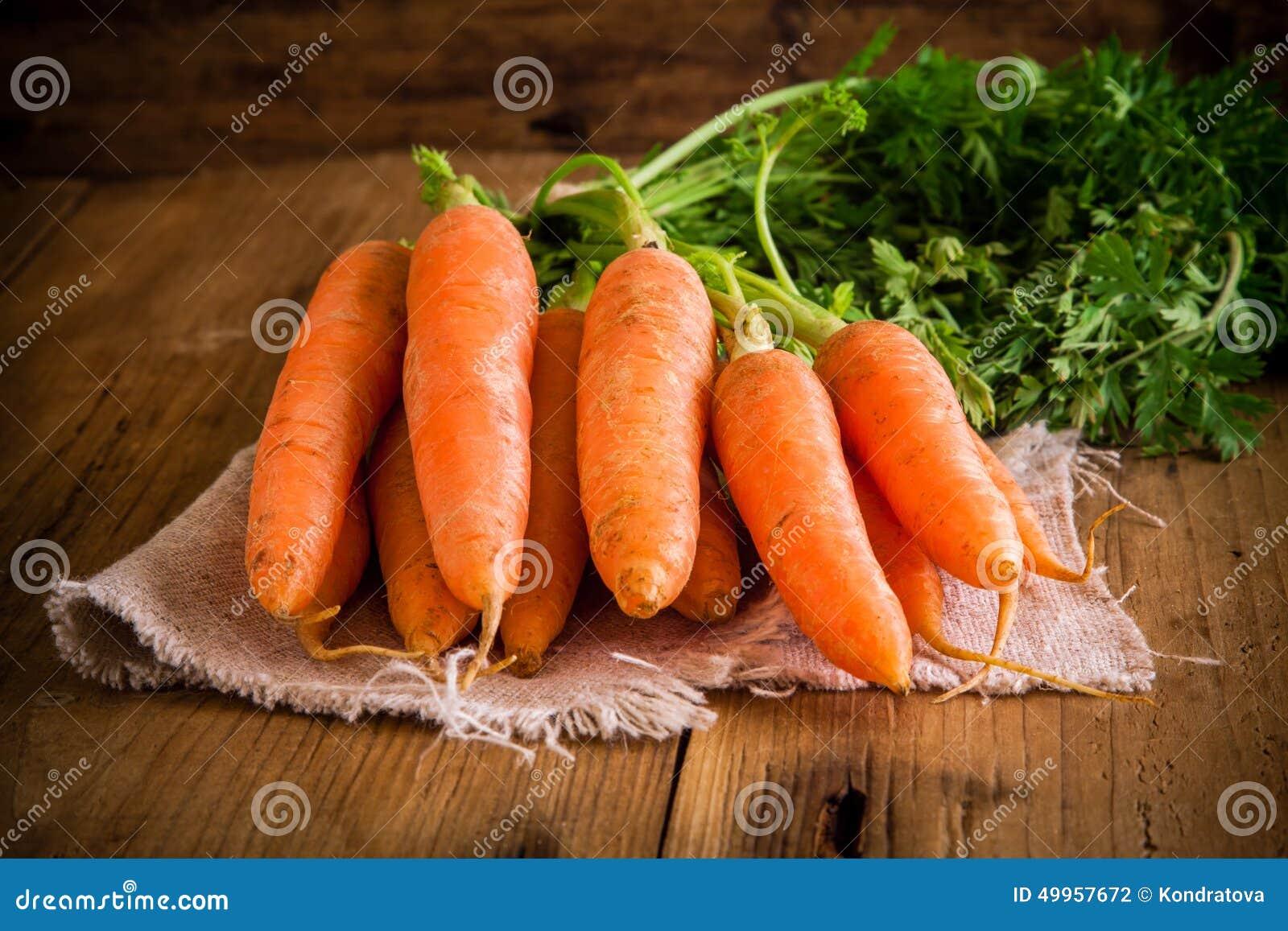 Grupo fresco das cenouras no fundo de madeira