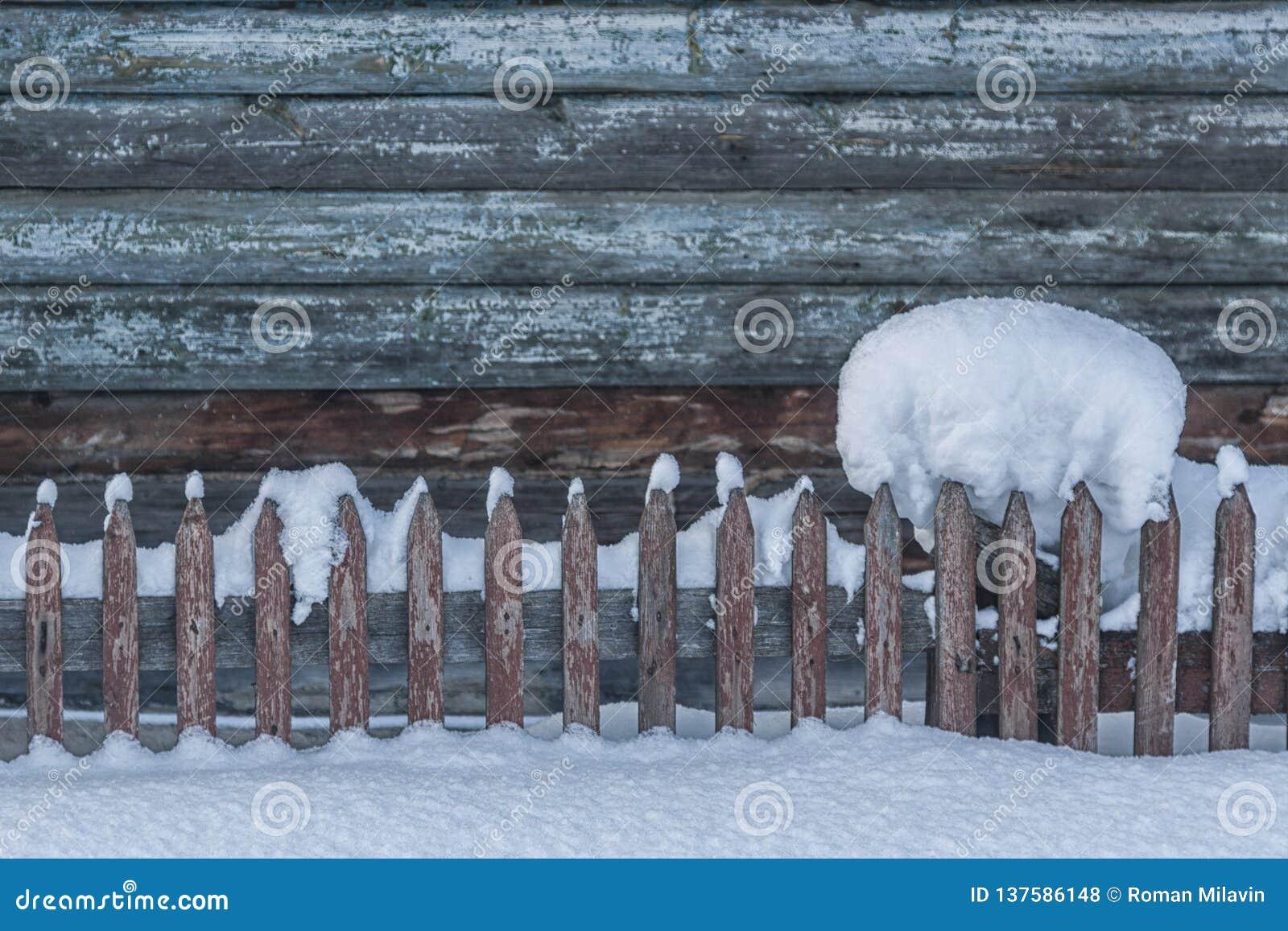Grupo hermoso de nieve en una cerca de madera con un contexto nevoso Hay una palizada de madera hermosa a continuación Navidad