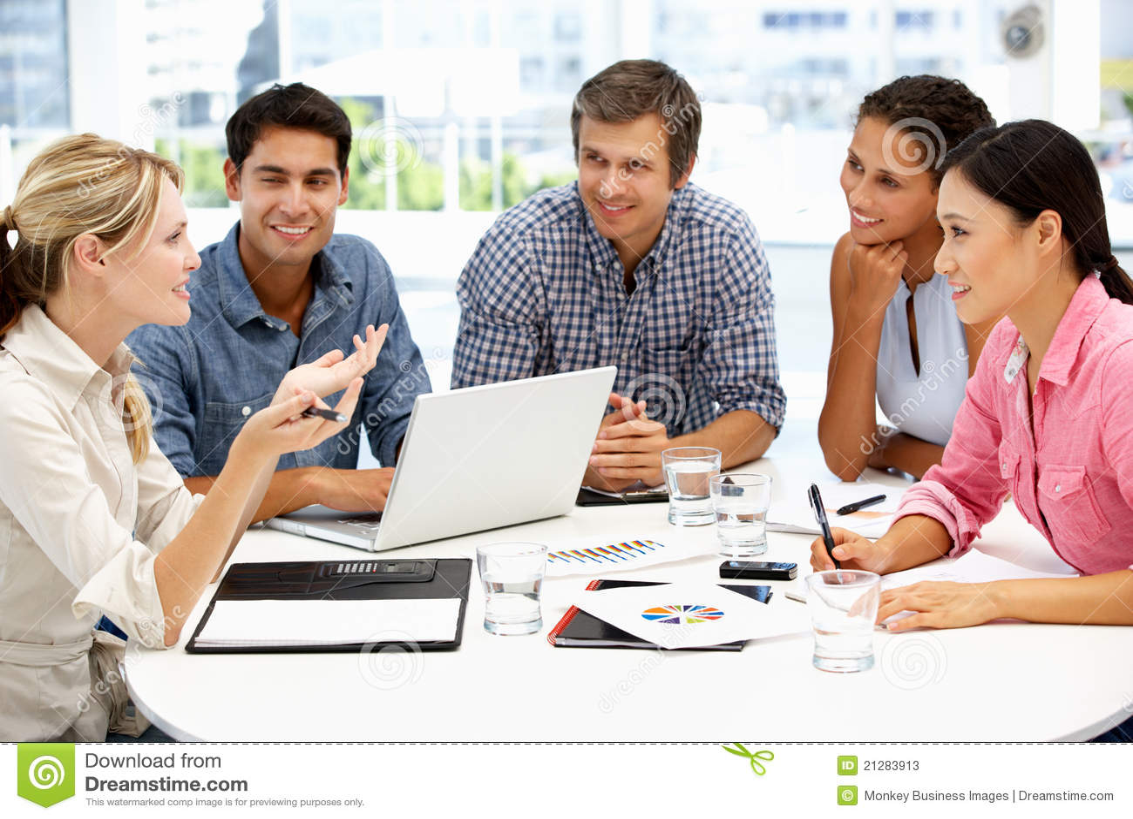Grupo mezclado alrededor del vector en la reunión de negocios