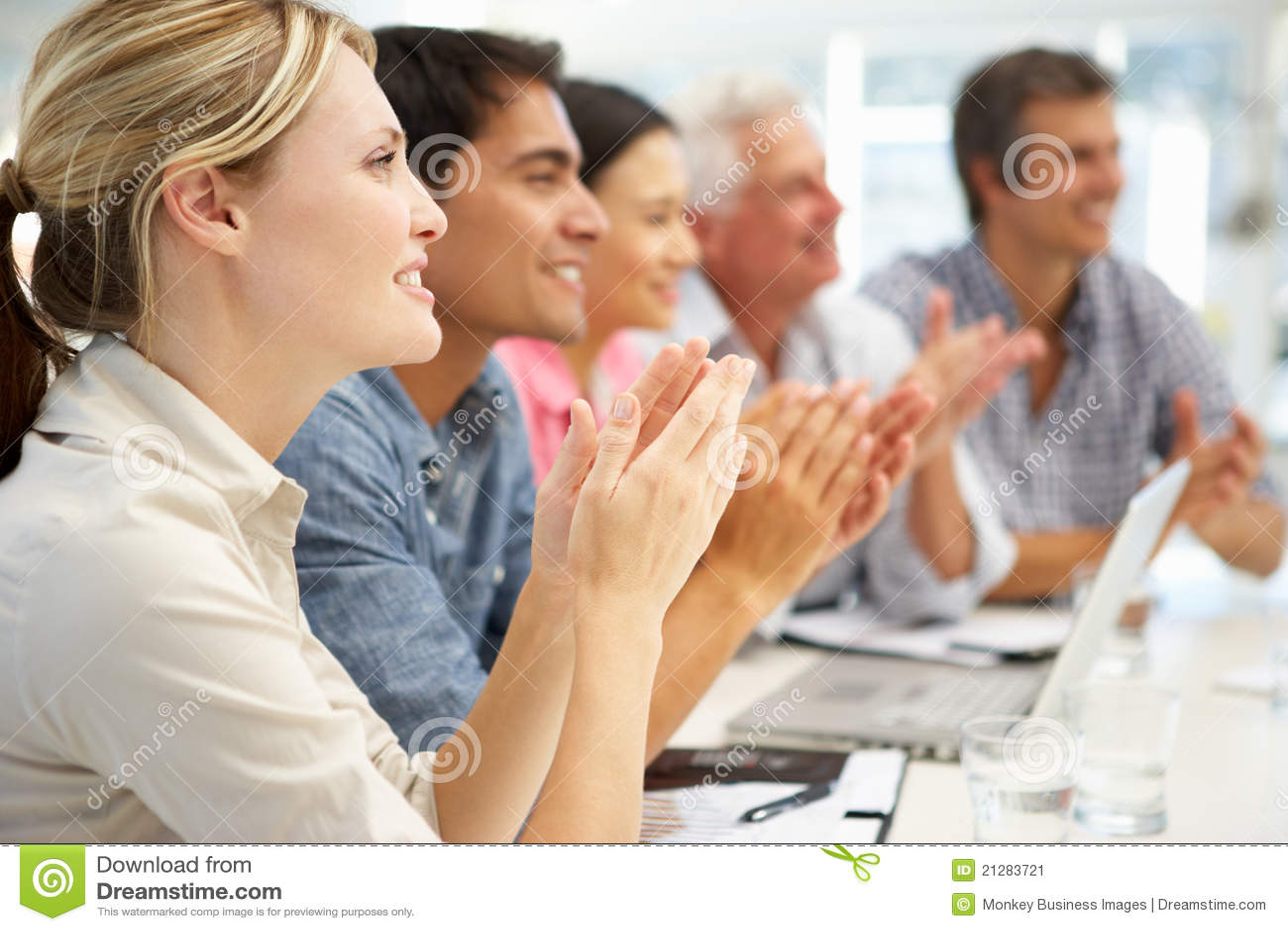Grupo mezclado que aplaude en la reunión de negocios