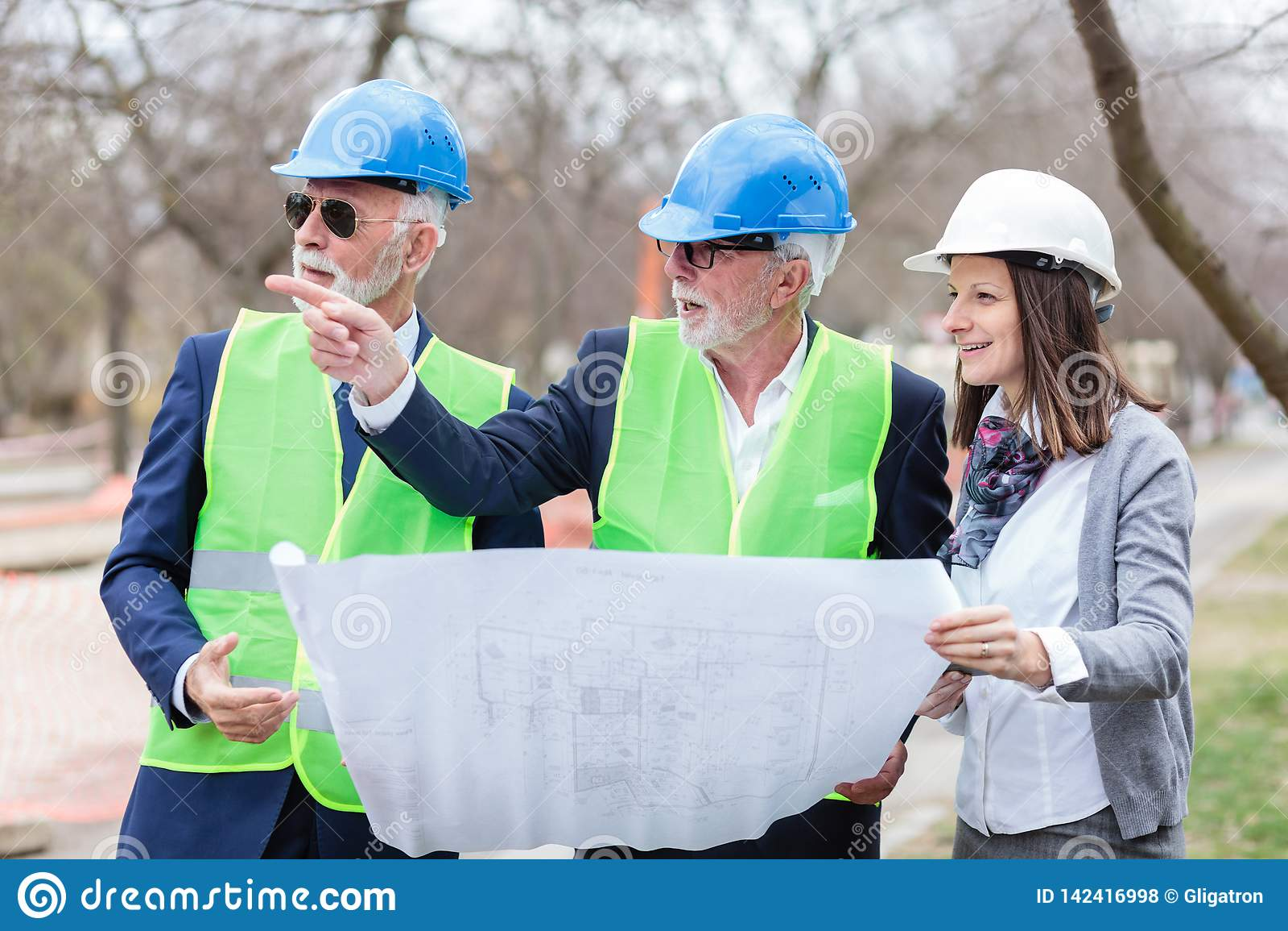 Grupo misturado de arquitetos e de sócios comerciais que discutem detalhes do projeto durante a inspeção de um canteiro de obras