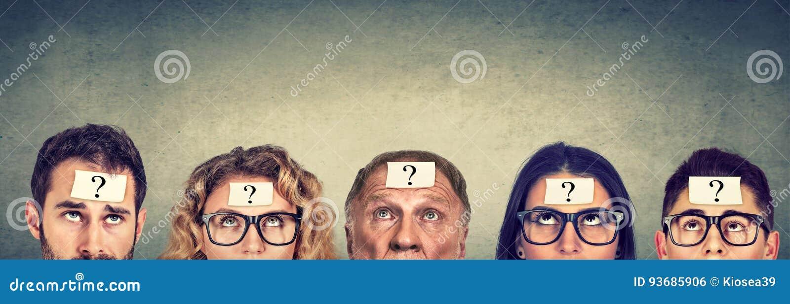 Grupo multiétnico de gente de pensamiento con el signo de interrogación que mira para arriba