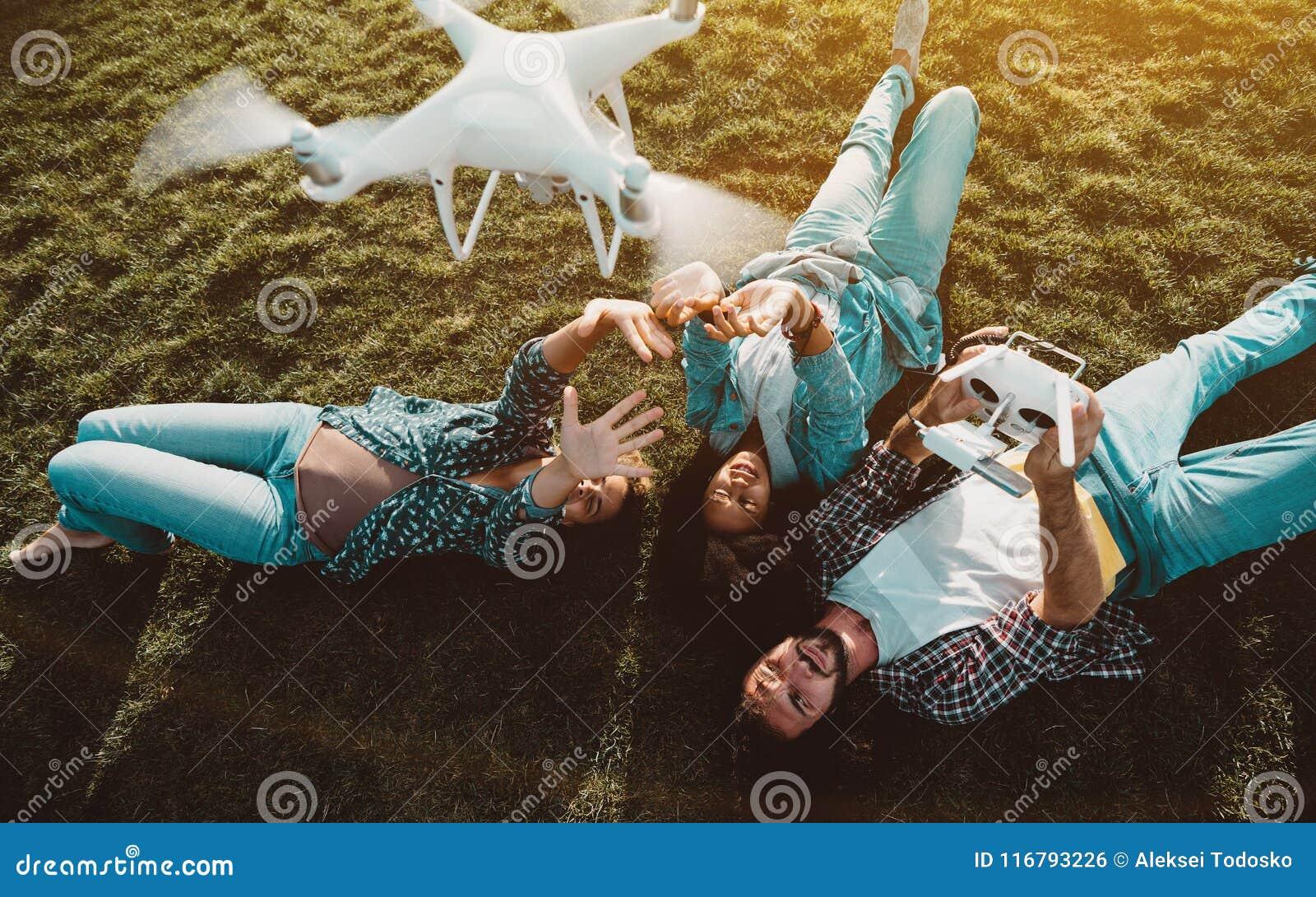 Grupo Multi-étnico de amigos no grama-lote com o multiro