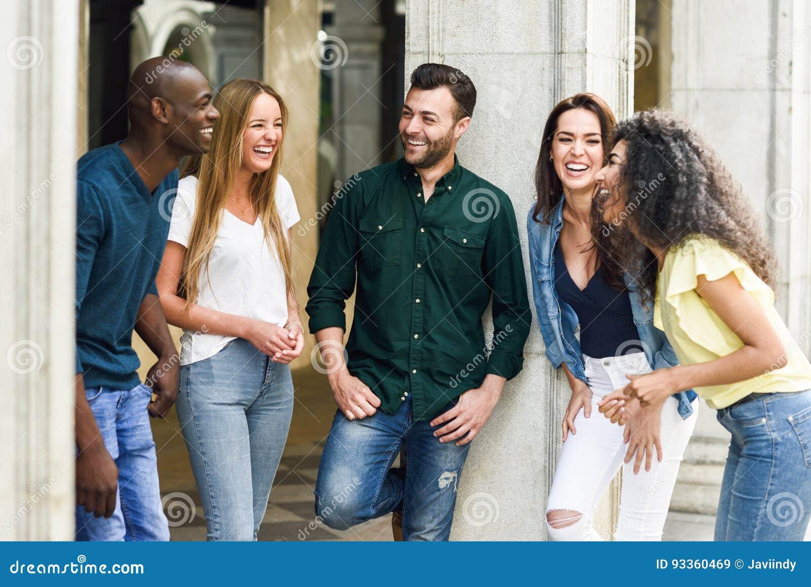 Grupo Multi-étnico de amigos que se divierten junto en backg urbano