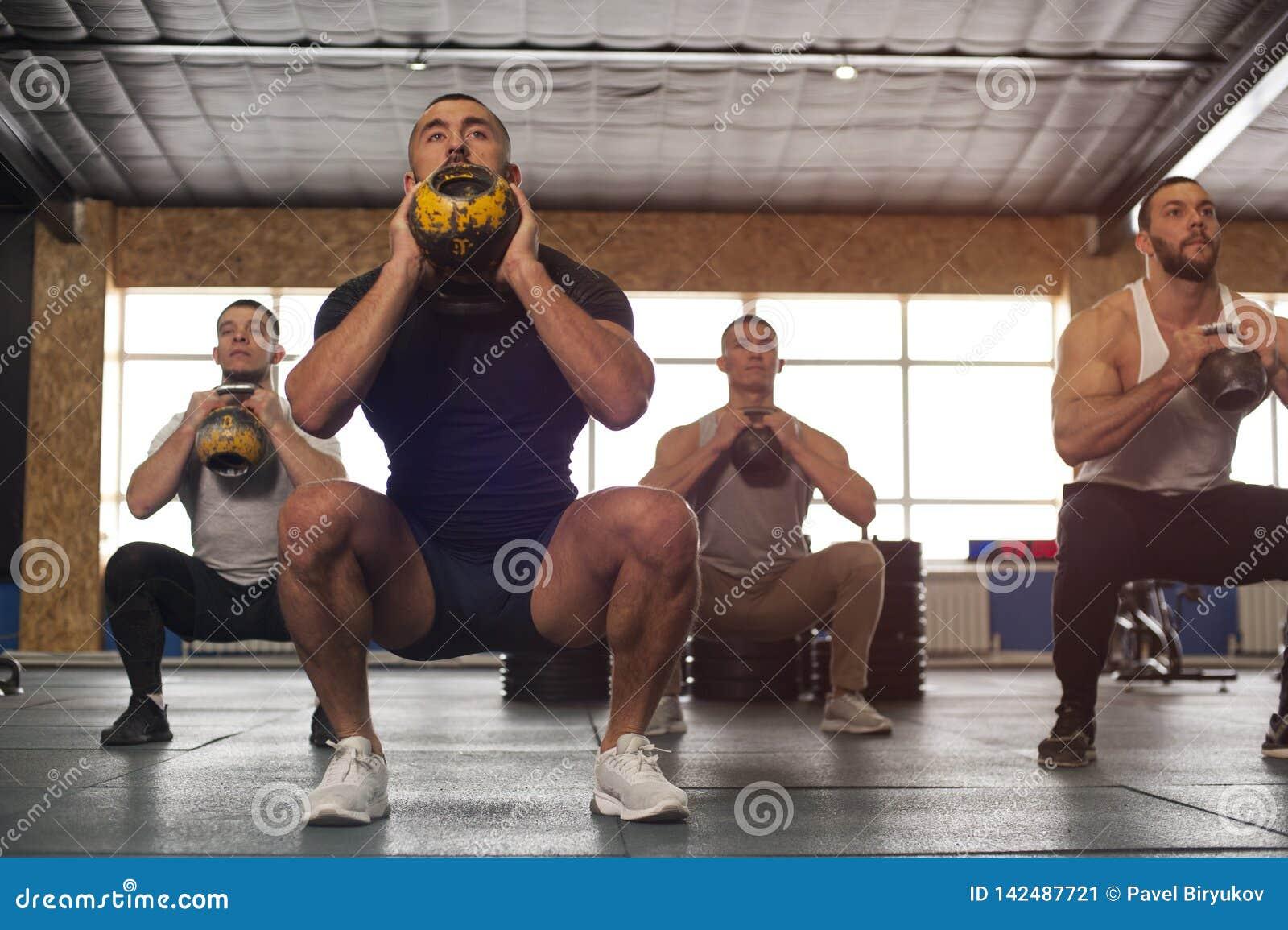 Grupo Multi-étnico de atletas de sexo masculino que entrenan en el gimnasio de Crossfit