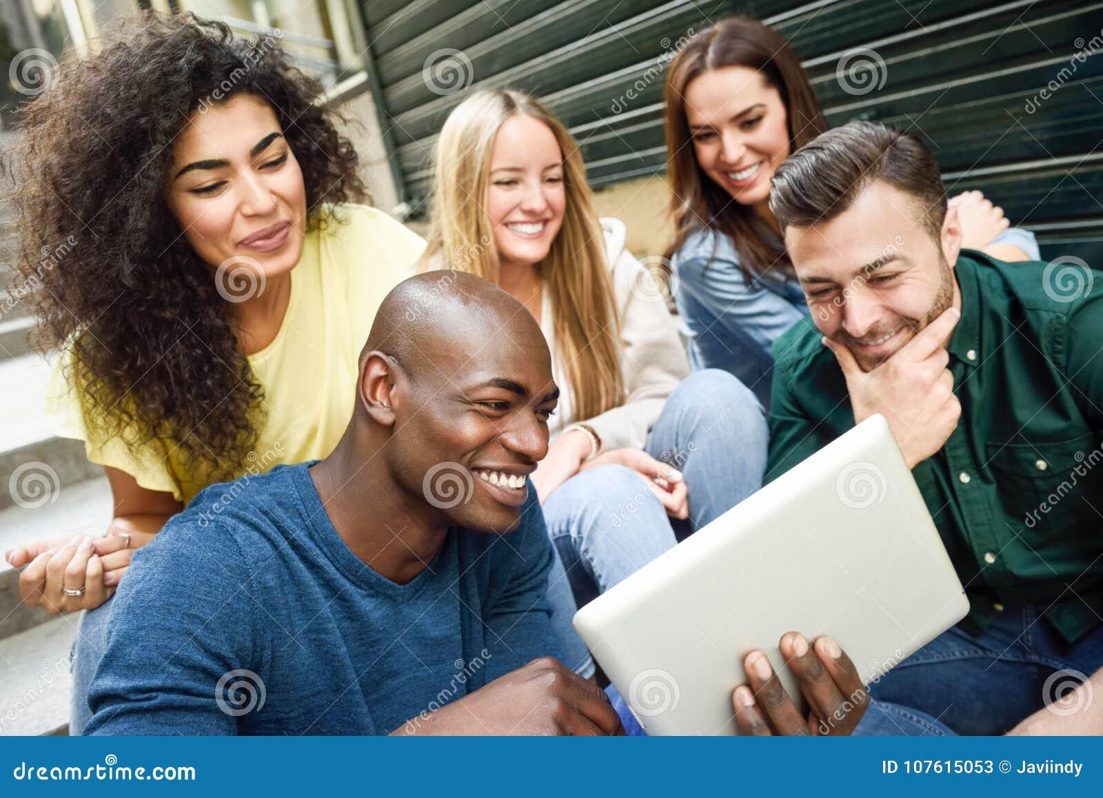 Grupo Multi-étnico de gente joven que mira una tableta