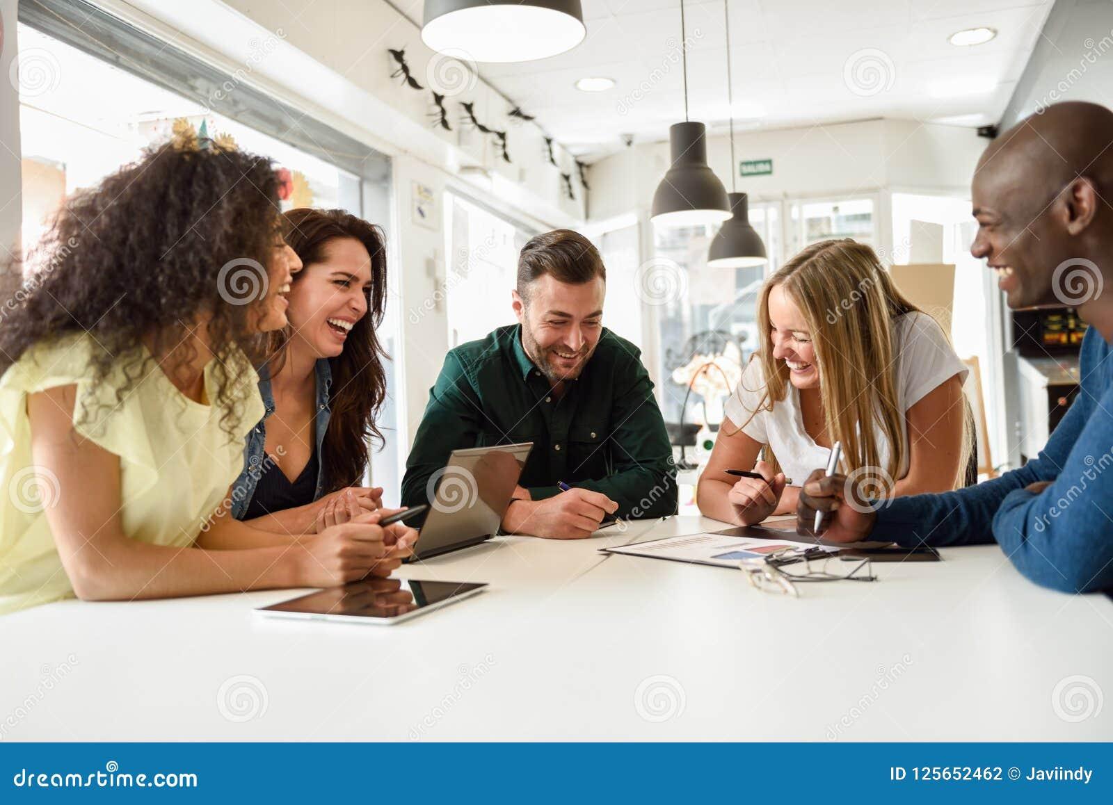 Grupo Multi-étnico de jovens que estudam junto no de branco