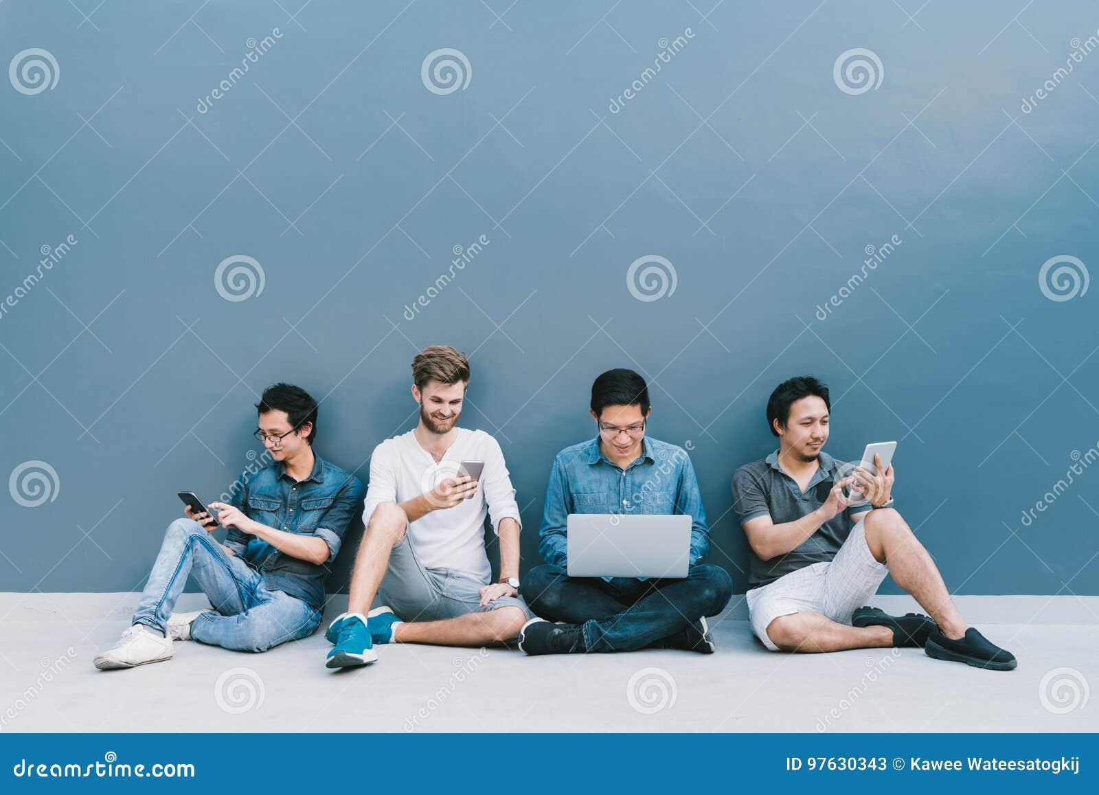 Grupo multi-étnico de quatro homens que usam o smartphone, laptop, tabuleta digital junto com o espaço da cópia na parede azul