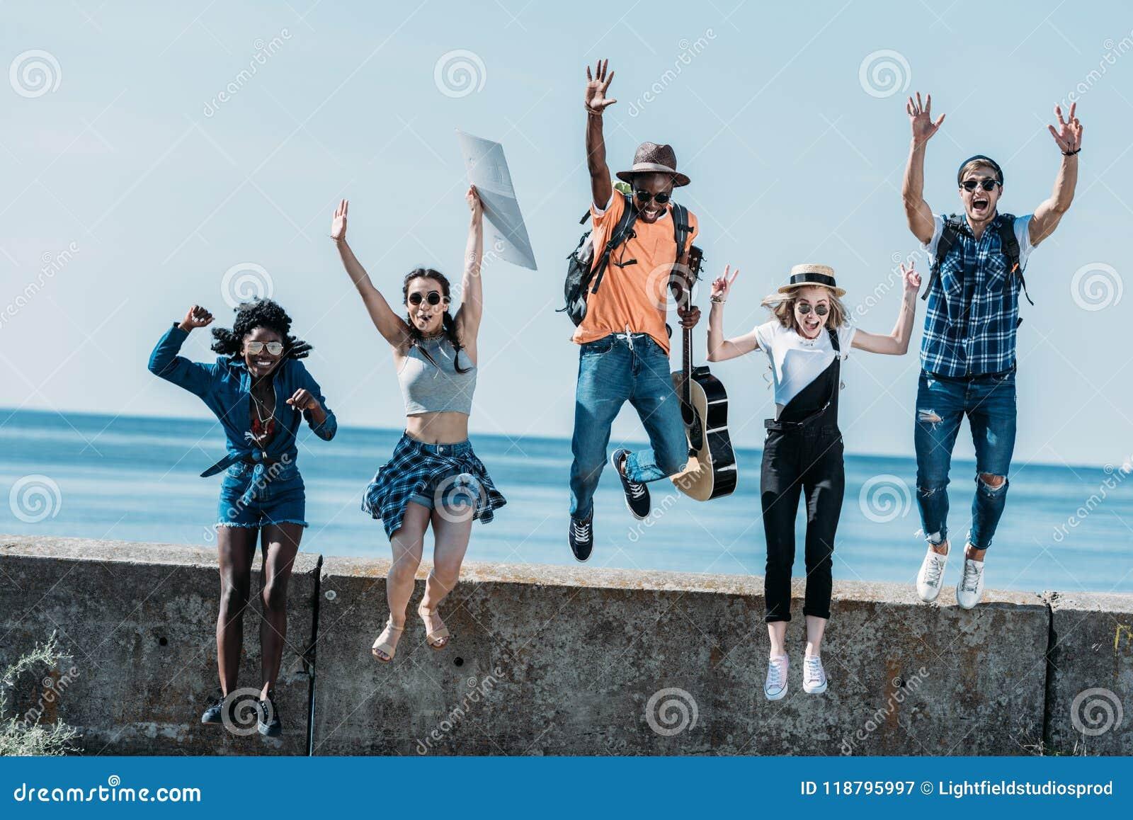 Grupo multicultural de salto joven de los amigos de