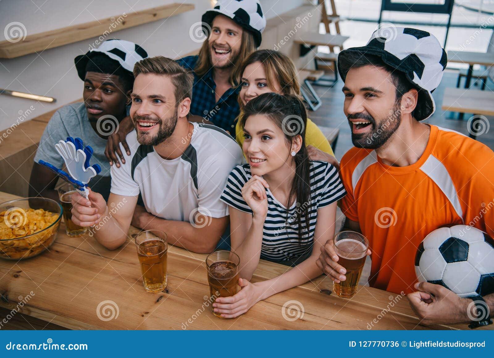 Grupo multicultural feliz de amigos em chapéus da bola de futebol que bebem a cerveja e que olham o fósforo de futebol