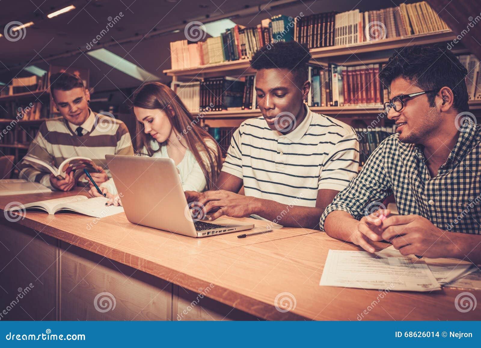 Grupo multinacional de estudiantes alegres que estudian en la biblioteca de universidad