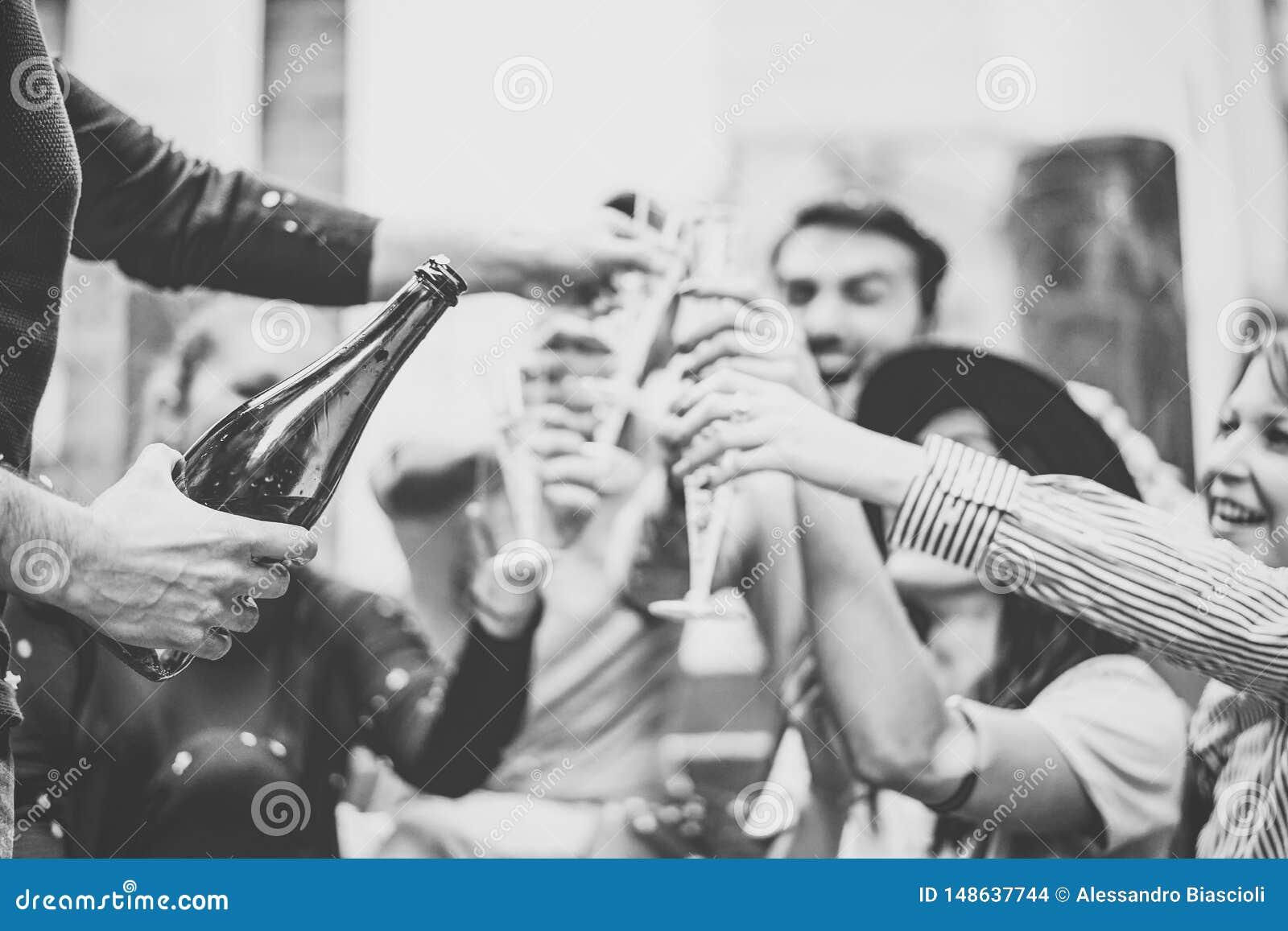 Grupo multirracial de amigos jovenes que se divierten que bebe y que tuesta los vidrios de champ?n en las escaleras de la univers