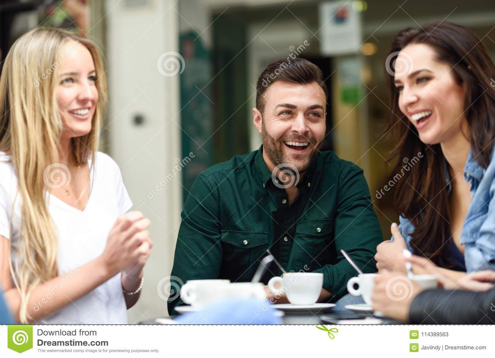 Grupo multirracial de amigos que comen un café junto