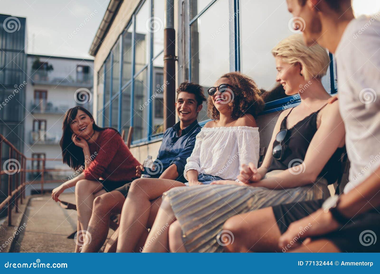 Grupo multirracial de amigos que se sientan en balcón y la sonrisa