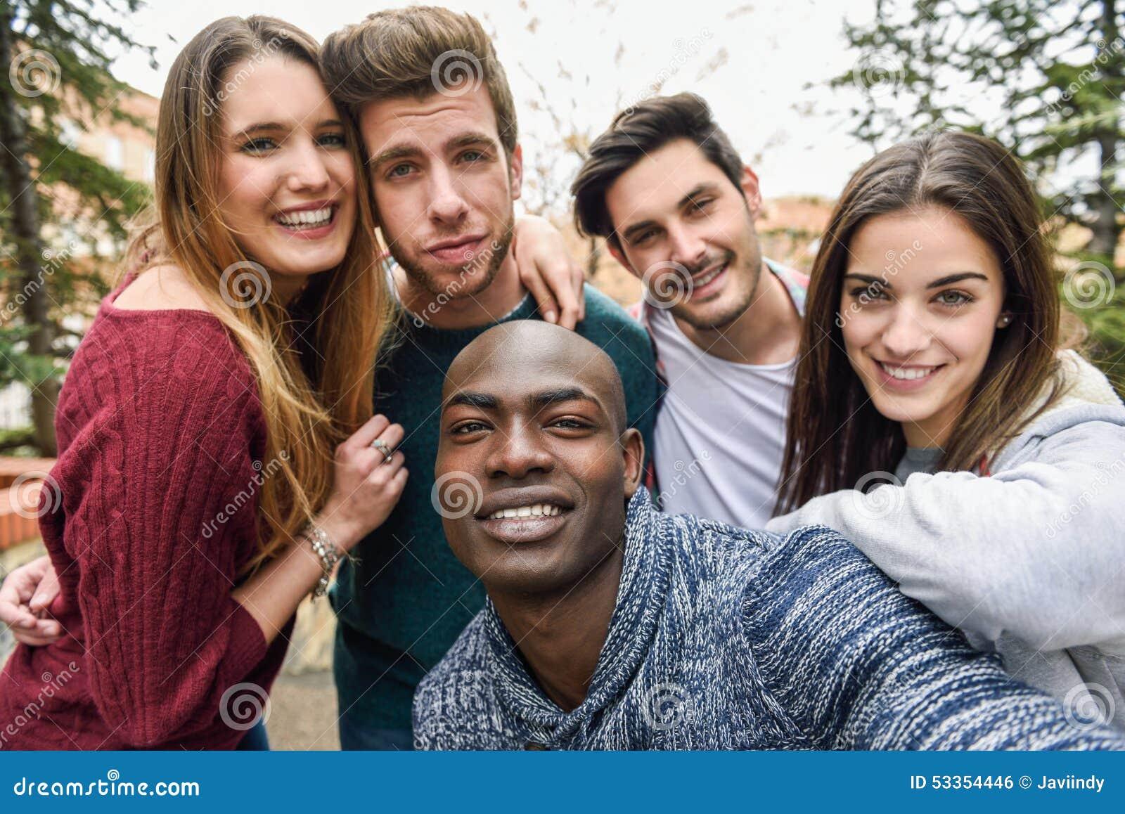 Grupo multirracial de amigos que toman el selfie