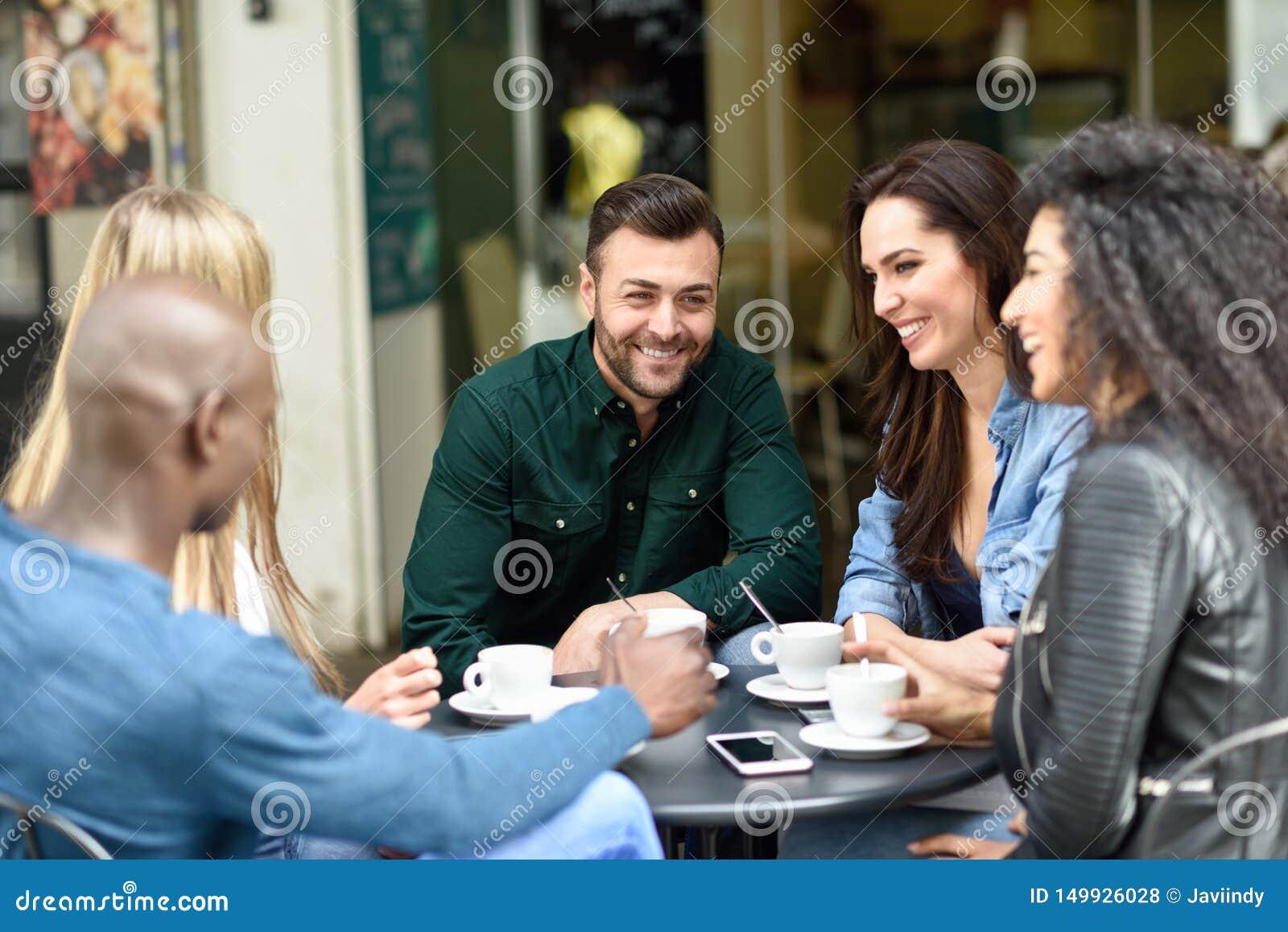 Grupo multirracial de cinco amigos que comen un caf? junto
