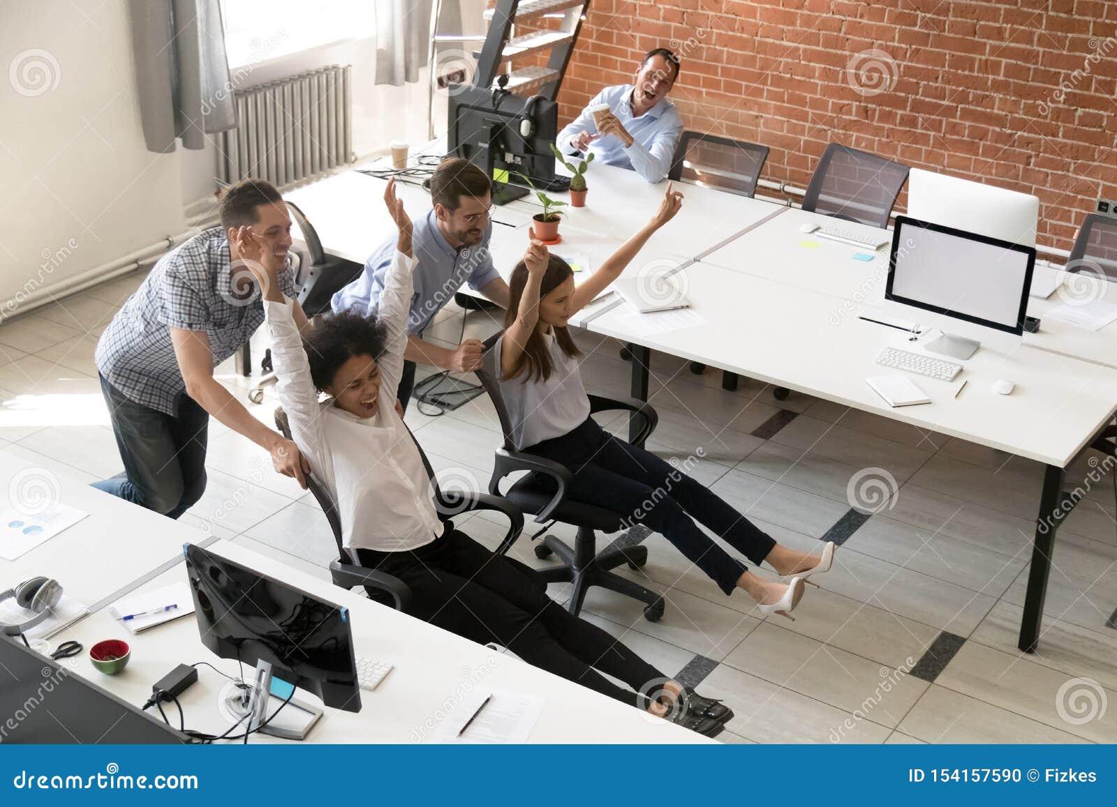 Grupo multirracial feliz de los colegas que se divierte junto en oficina