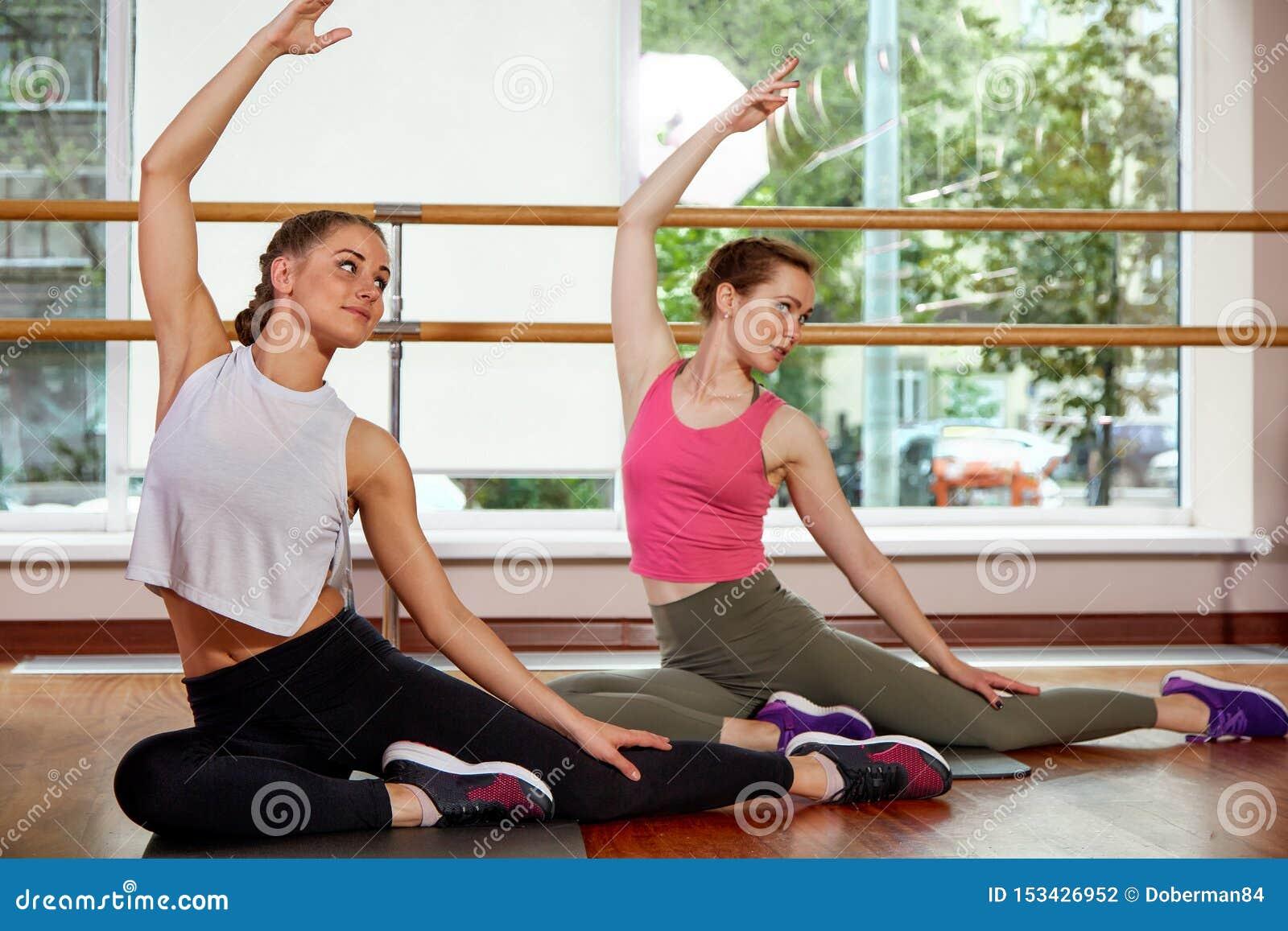 Grupo multirracial feliz de muchachas y de cristales hermosos jovenes, sonrientes en la ropa de deportes, haciendo ejercicios de