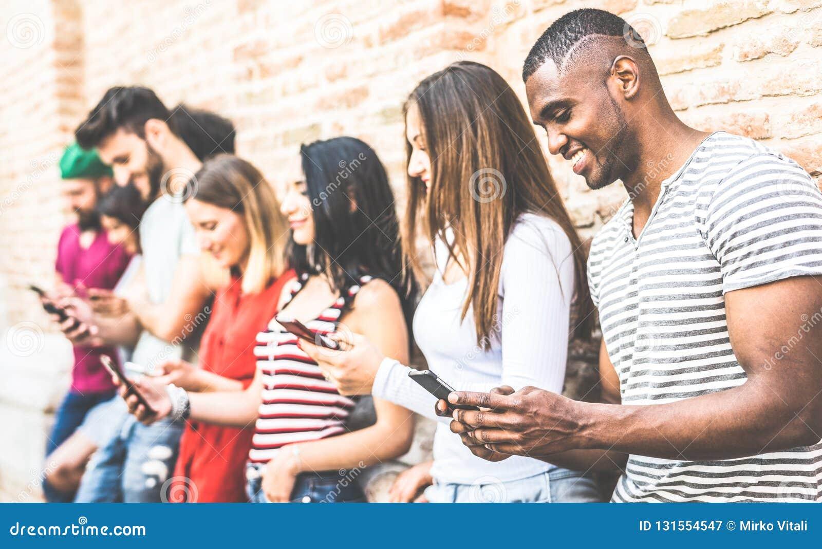 Grupo multirracial usando smartphone en la rotura de la Universidad - gente de los amigos de Millenial enviciada por los teléfono