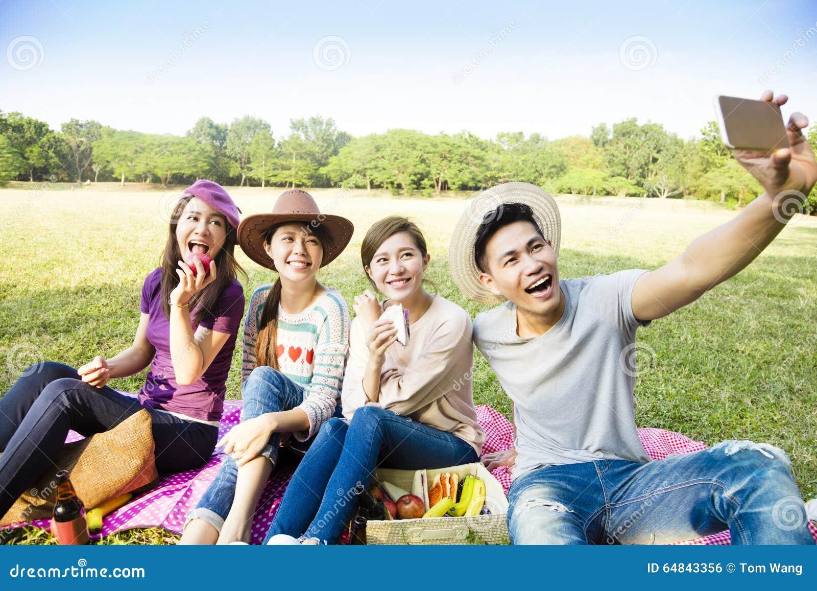 Grupo novo feliz que faz o selfie pelo telefone esperto