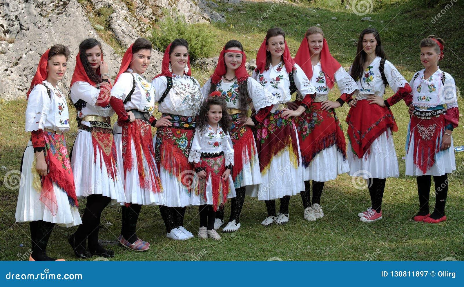 Grupo popular fêmea que levanta com os trajes tradicionais coloridos de A