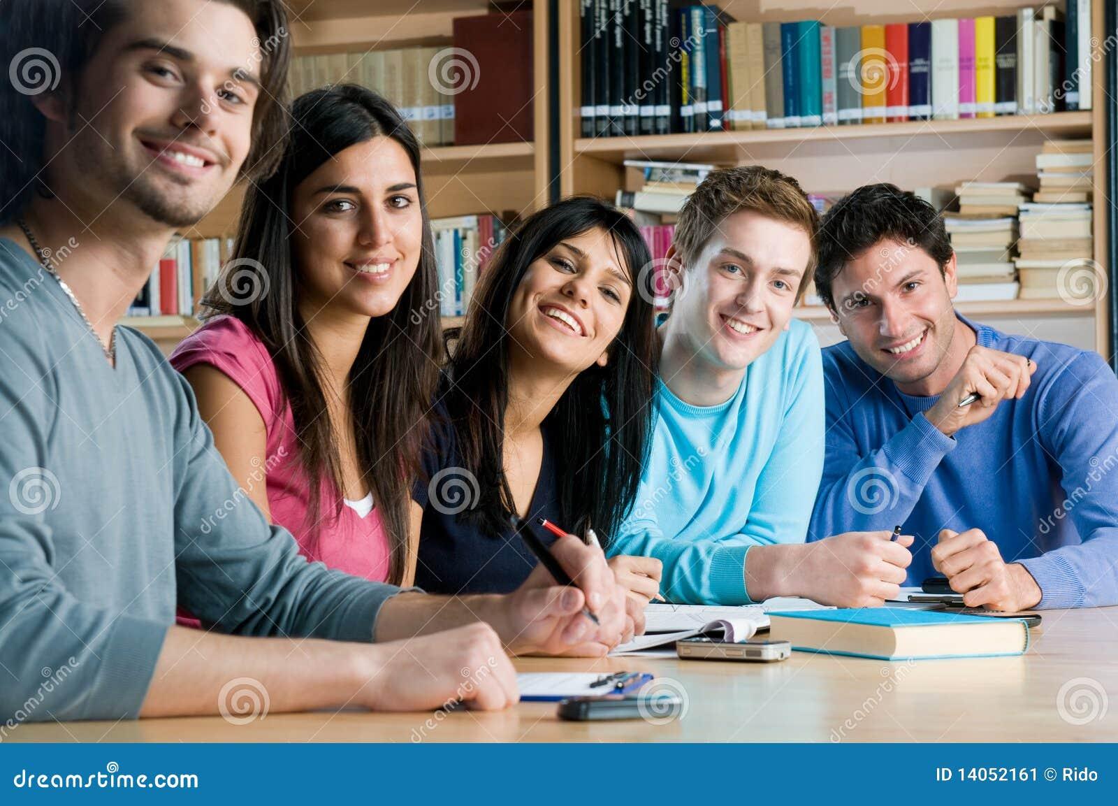 Grupo sonriente de estudiantes en una biblioteca