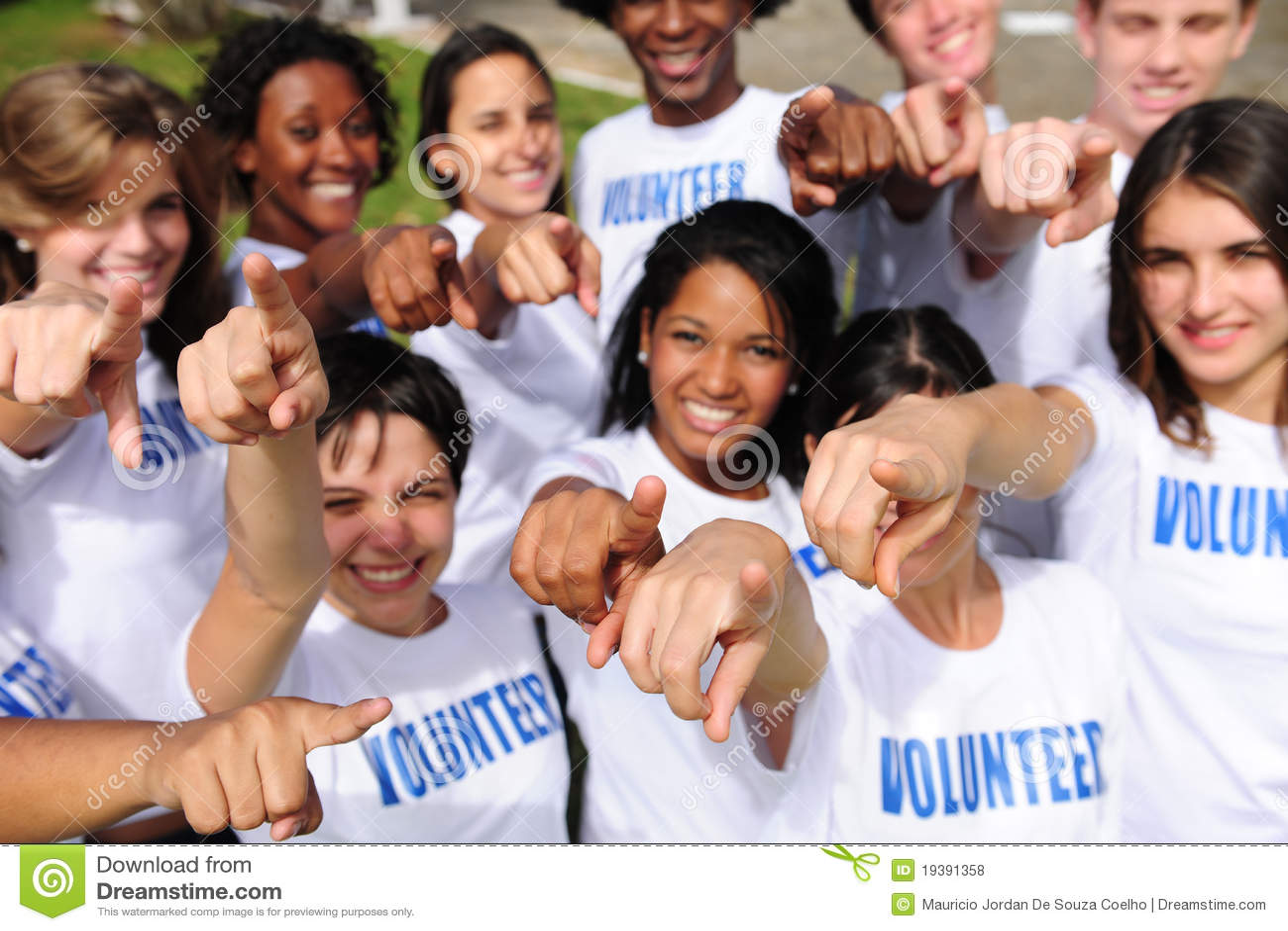 Grupo voluntario feliz que señala hacia cámara
