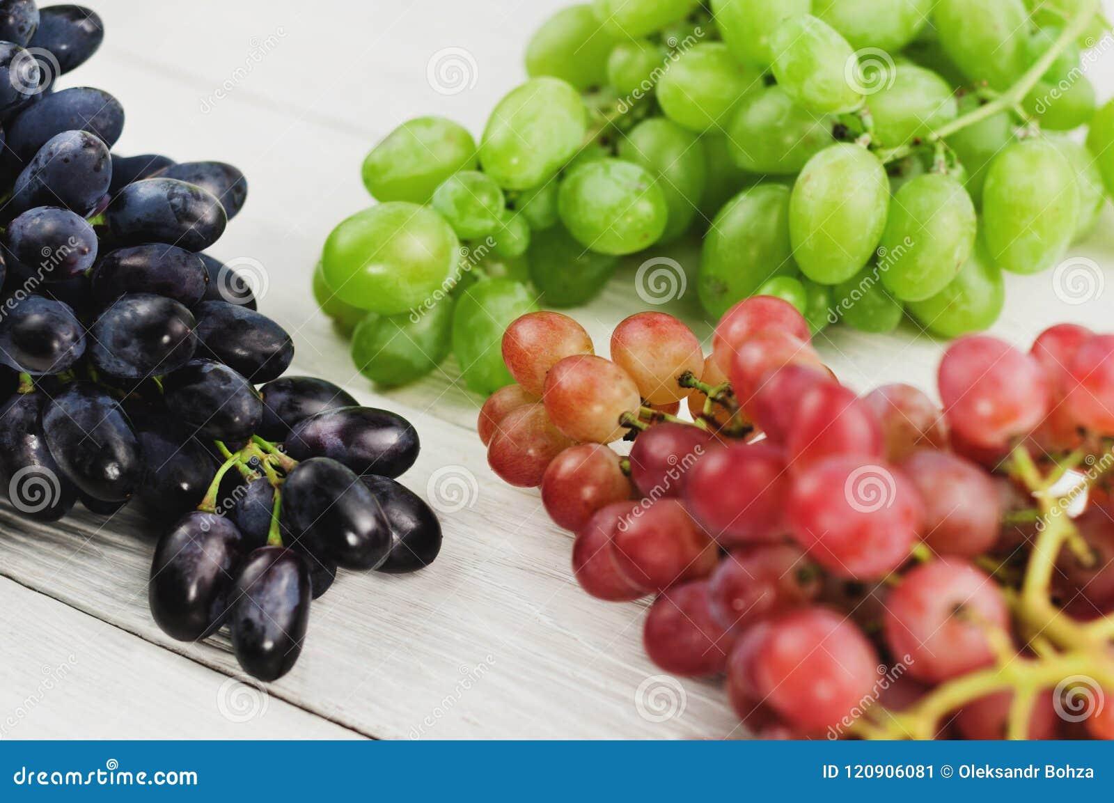 Grupos de uvas azuis e cor-de-rosa e verdes maduras frescas em pranchas brancas de madeira velhas