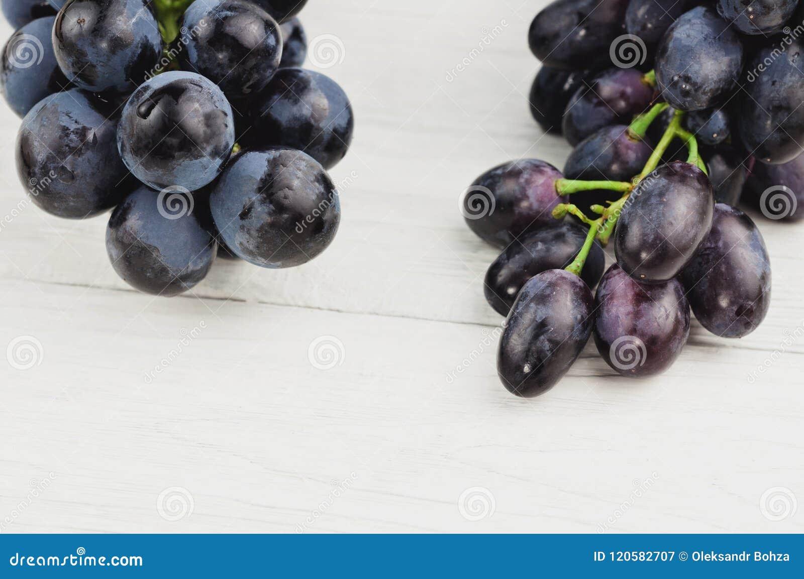 Grupos de uvas azuis maduras frescas em pranchas brancas de madeira velhas
