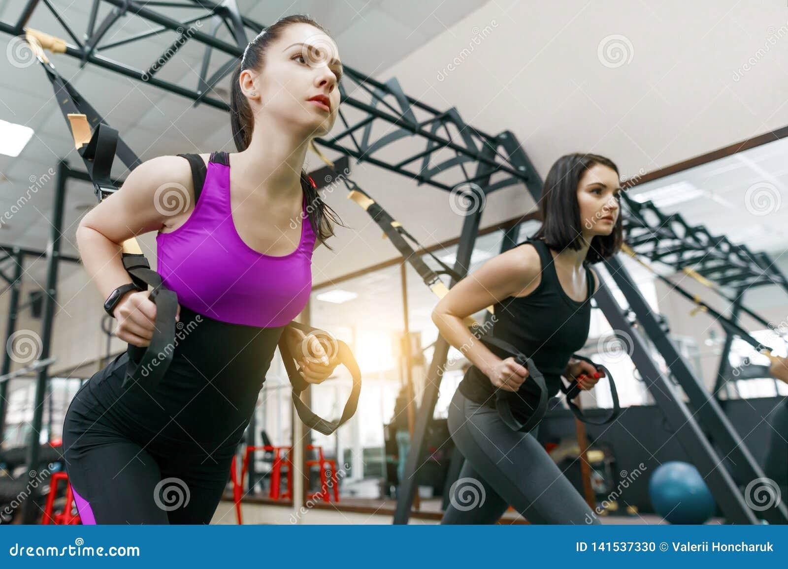 Grupowy szkolenie z pętlami w gym, dwa młodej atrakcyjnej sprawności fizycznej kobiety robi krzyża napadowi z patka systemem Spor