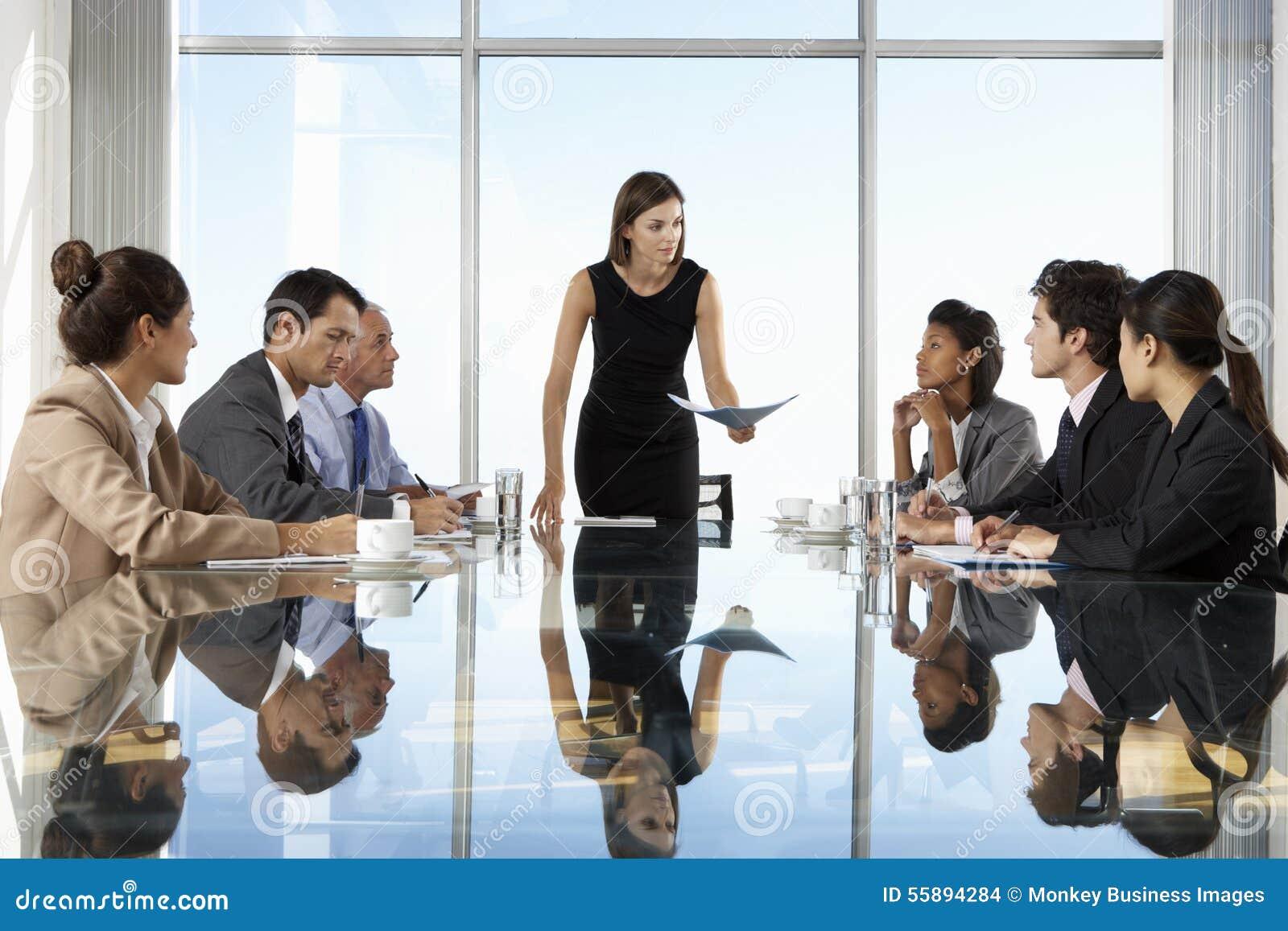 Grupp av affärsfolk som har styrelsemötet runt om den Glass tabellen