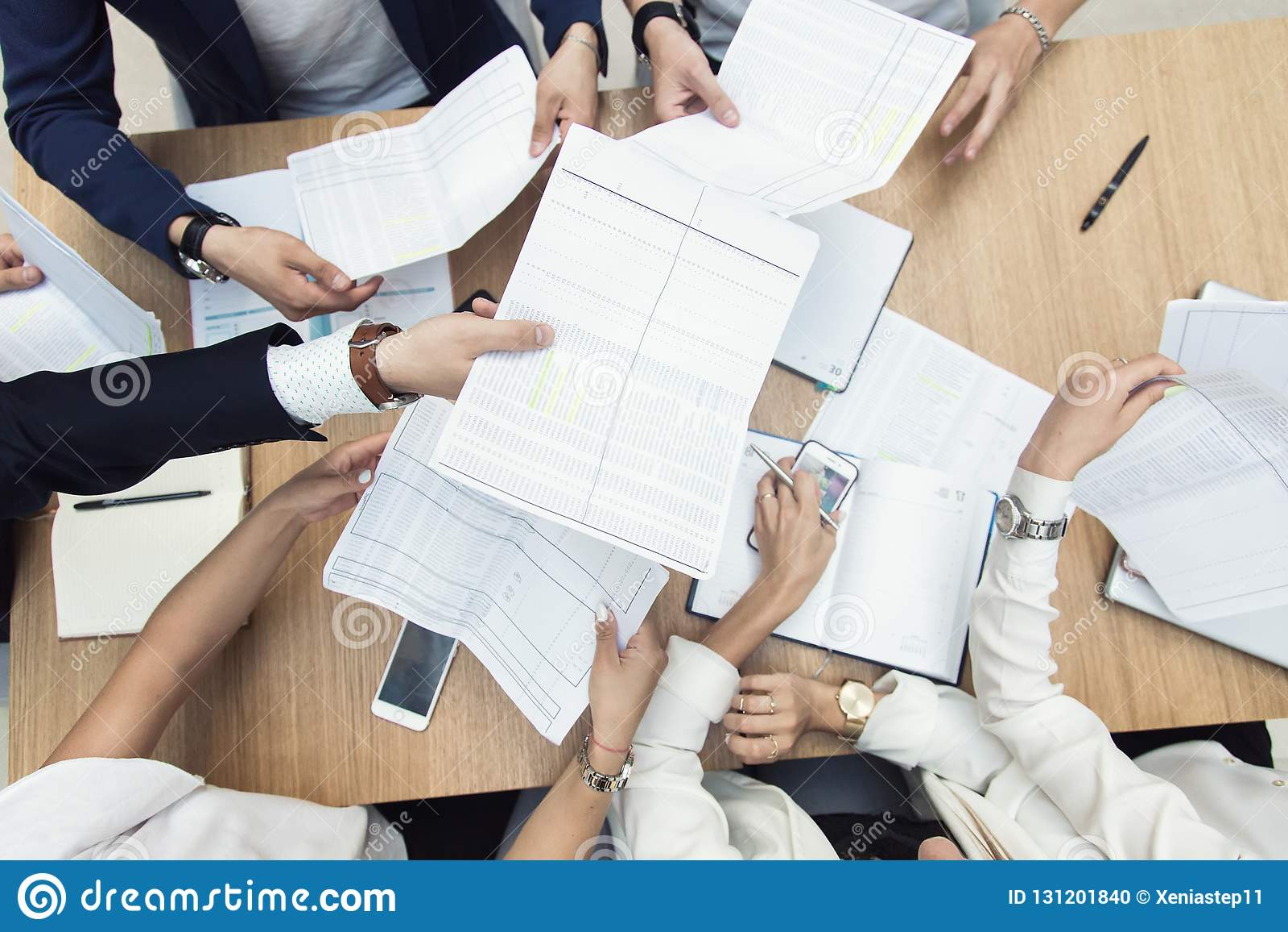 Grupp av aff?rsm?tet p? tabellen i det moderna kontoret, lagarbetet och de olika h?nderna som sammanfogar tillsammans aff?rsf?rh?