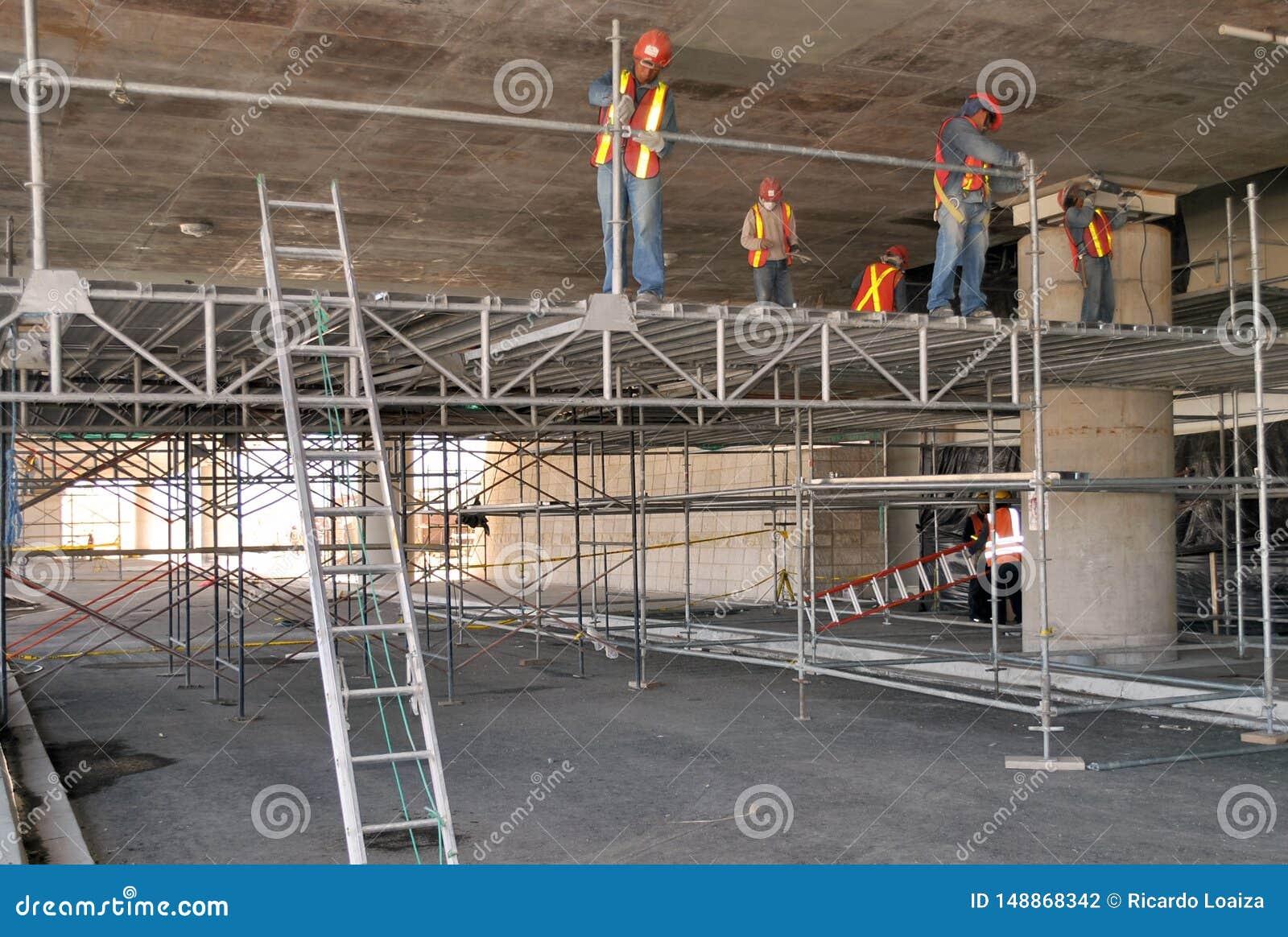 Grupp av arbetare som monterar materialet till byggnadsst?llning i deras workspace