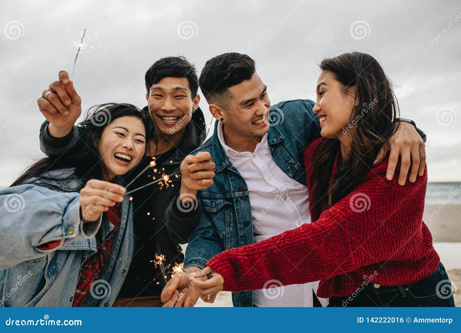 Grupp av asiatiska vänner som firar nytt års den ay stranden för dag